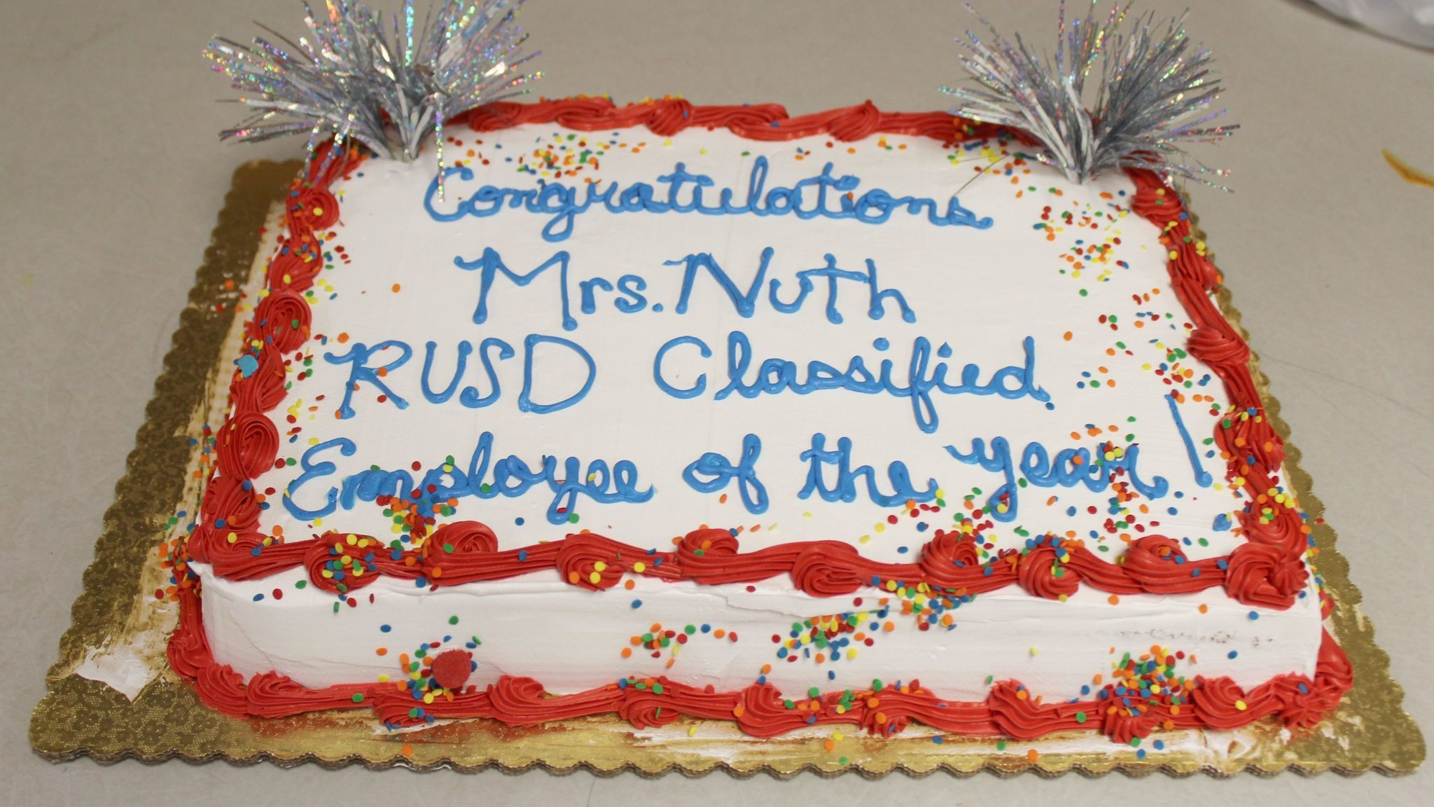 Students and staff share a piece of cake celebrating Nuth.
