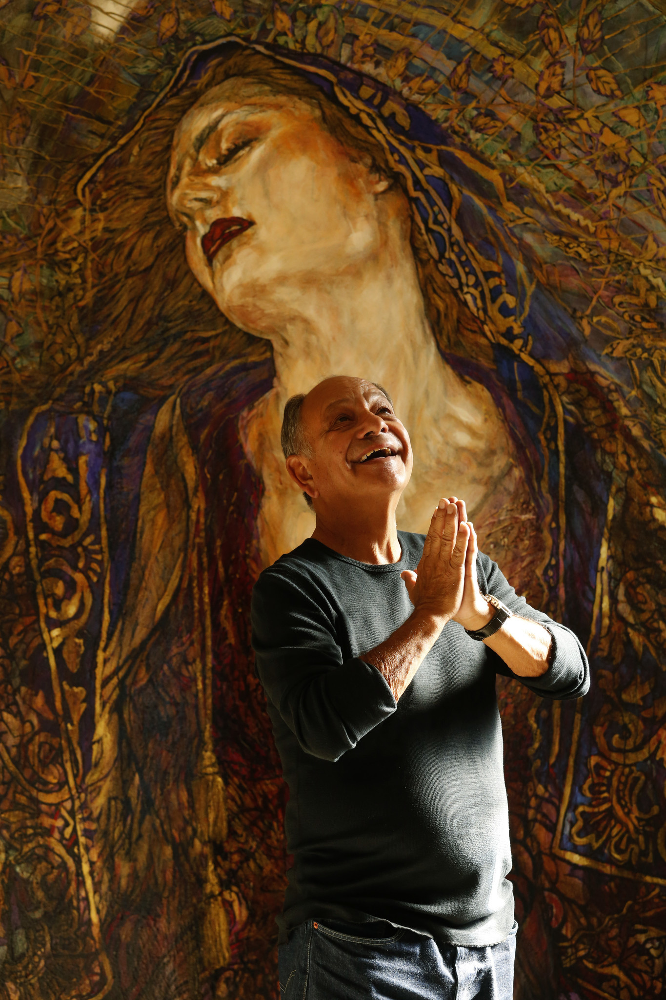 "Cheech Marin strikes an angelic pose in front of a painting by Chicano artist George Yepes entitled, ""Axis Bold As Love,"" in his Pacific Palisades home on March 27."