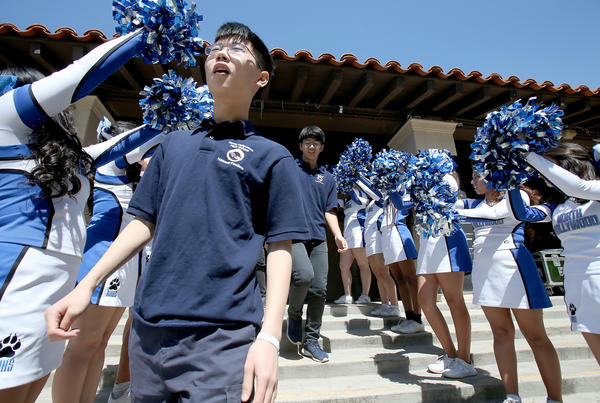 Alexander Ke left, Eugene Woo and other members of the North Hollywood High School cyber defense team are cheered at a pep rally. (Luis Sinco / Los Angeles Times)