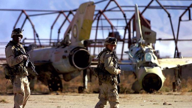 In December 2001, U.S. Army soldiers from the 10th Mountain Division patrol an airfield littered wit