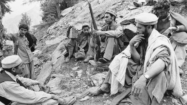 In February 1980, mujahedin listen to the radio as they rest in the rocky, mountainous area of Afgh