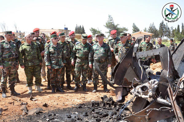 A handout picture released April 7 by the official Syrian Arab News Agency reportedly shows Syrian forces viewing damage at the Shayrat air field. (Syrian Arab News Agency)