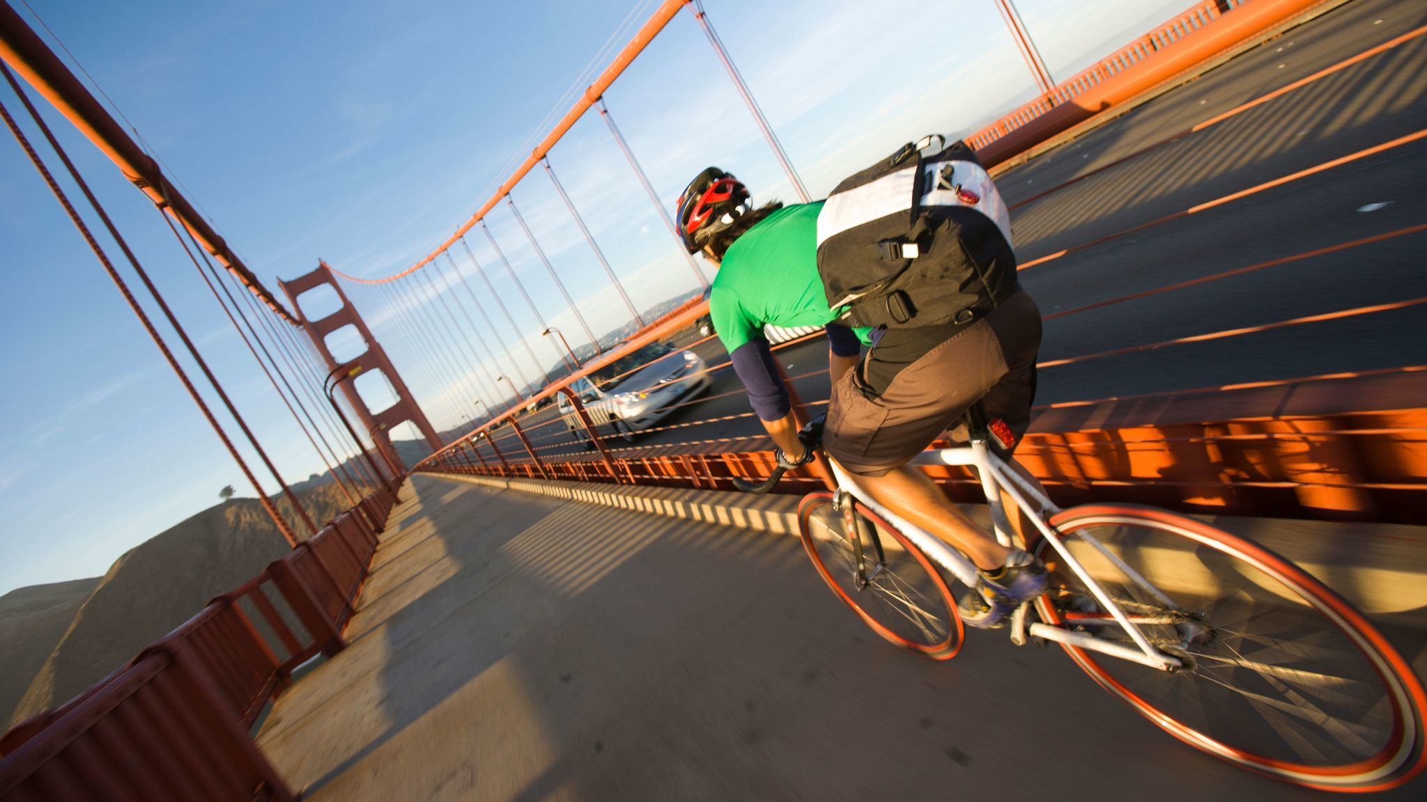 A solo cyclist crossing the Golden Gate Bridge at sunset on the commute home to the Marin near San Francisco, California.