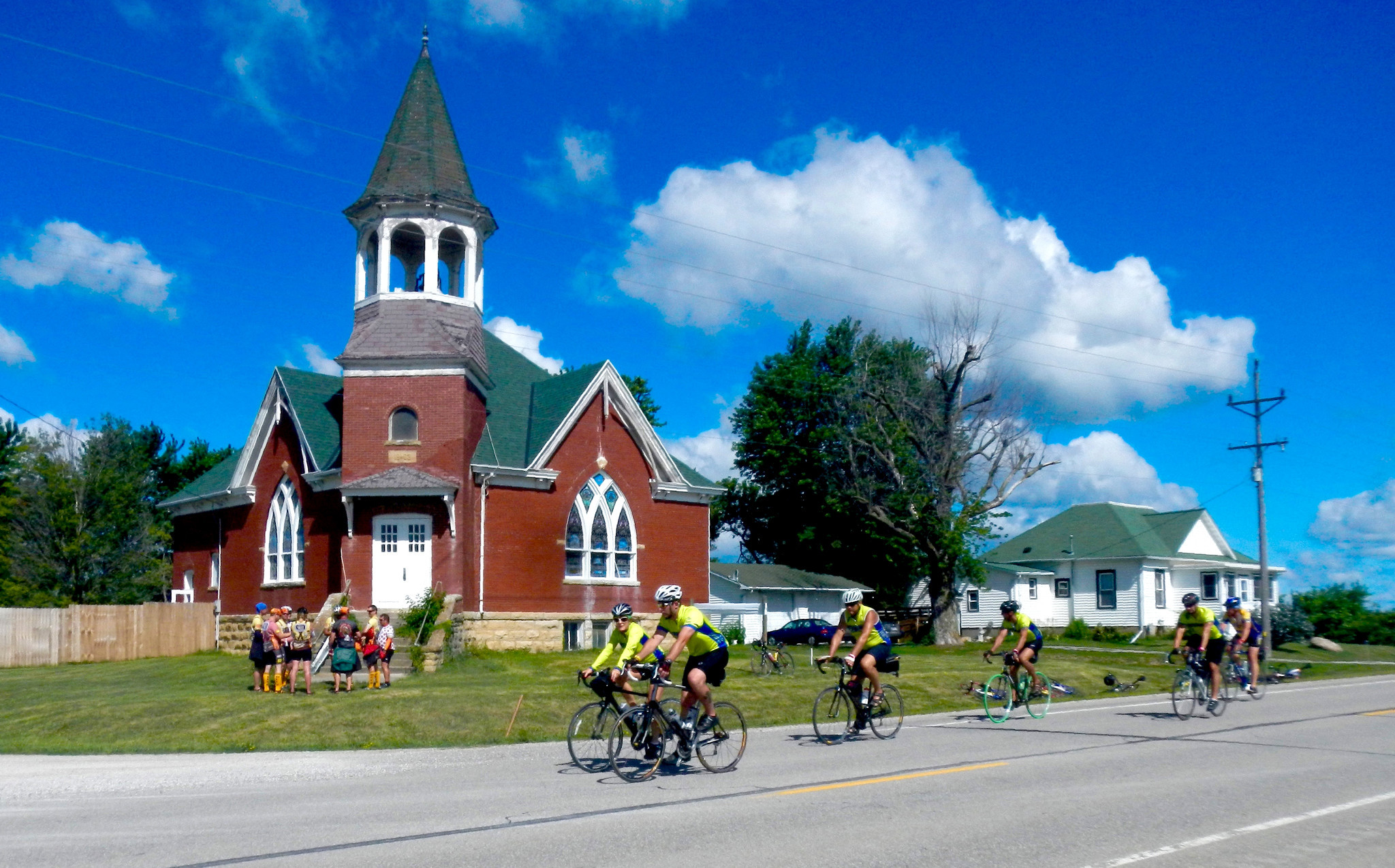 Cyclists on an Iowa RAGBRAI tour riding by a church in a small town in eastern Iowa. Some of the riders have stopped to check out the church.
