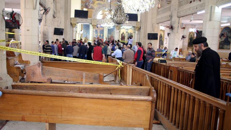 A Coptic priest views the damage as security personnel investigate inside St. George's Church in Tan