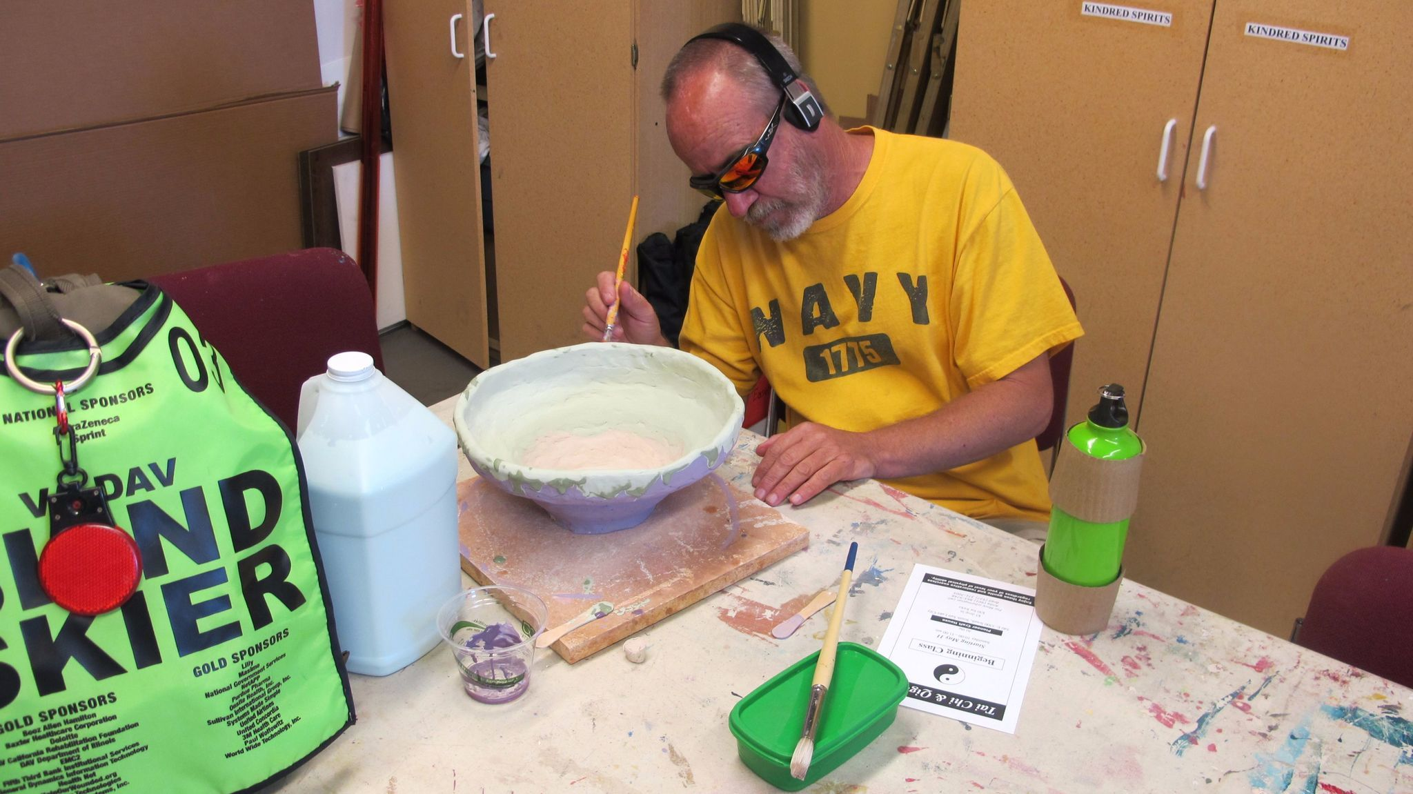 A blind veteran adds glaze to a pot he created in a ceramics sculpture workshop at Art Access in Salt Lake City.