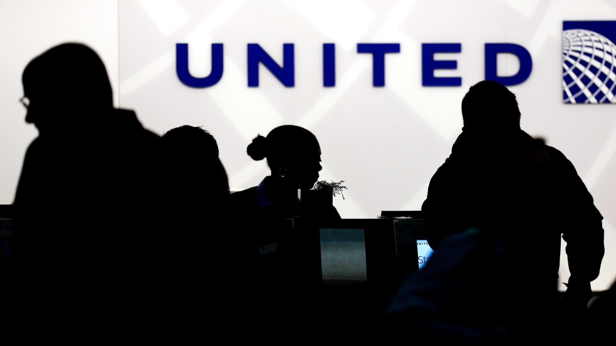 Travelers check in at the United Airlines ticket counter in O'Hare International Airport in Chicago. The carrier is reviewing its policy for overbooking.