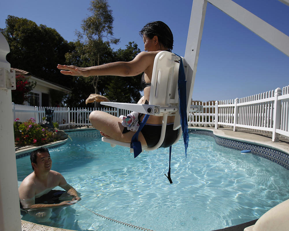 Superior Redlawsk Is Lifted Into A Swimming Pool For Therapy While Her Husband Waits  In The Water On June 13, 2010 In Los Angeles. (Gina Ferazzi / Los Angeles  Times) ...
