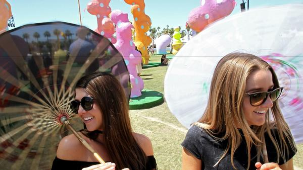 "Madelyn Maresca, 21, and Kaitlin Mason, 21, stroll through a work of art called ""Chiaozza Garden"" on Friday, Day One of the Coachella Valley Music and Arts Festival in Indio. (Luis Sinco / Los Angeles Times)"