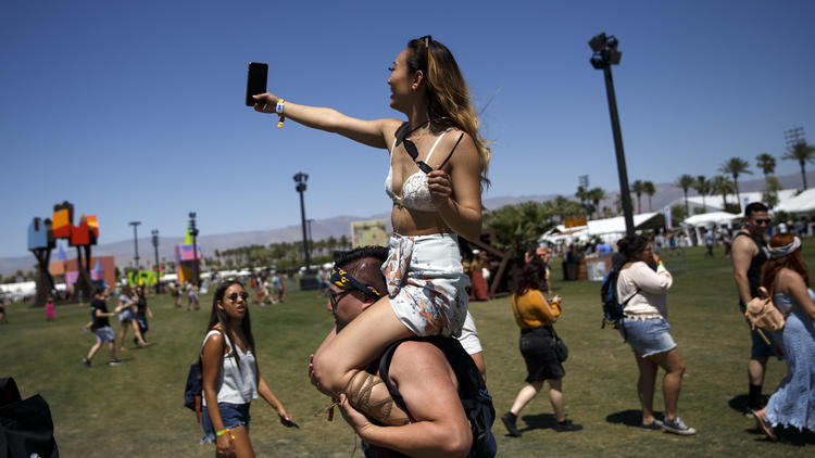 Barbara Huynh of San Jose takes a selfie while atop the shoulders of Anthony Seto of Los Angeles on Friday at Coachella. (Patrick T. Fallon / For The Times)