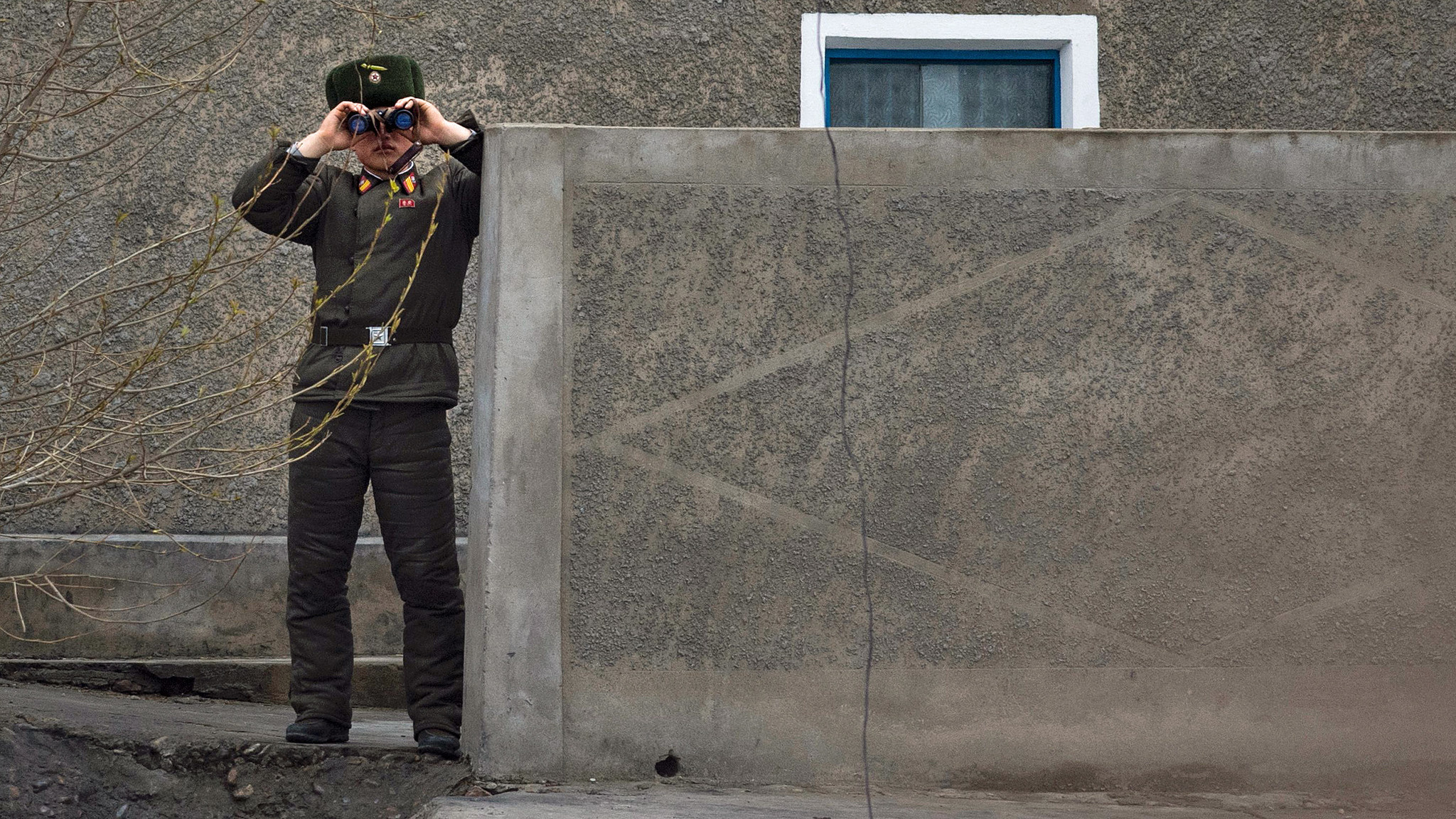A North Korean soldier looks across the banks of the Yalu river into China.
