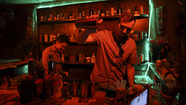 PDT bartenders Christian Hurtado, left, and Adam Schmidt work behind the bar at PDTiki at the Coachella festival. (Patrick Fallon / For The Times)