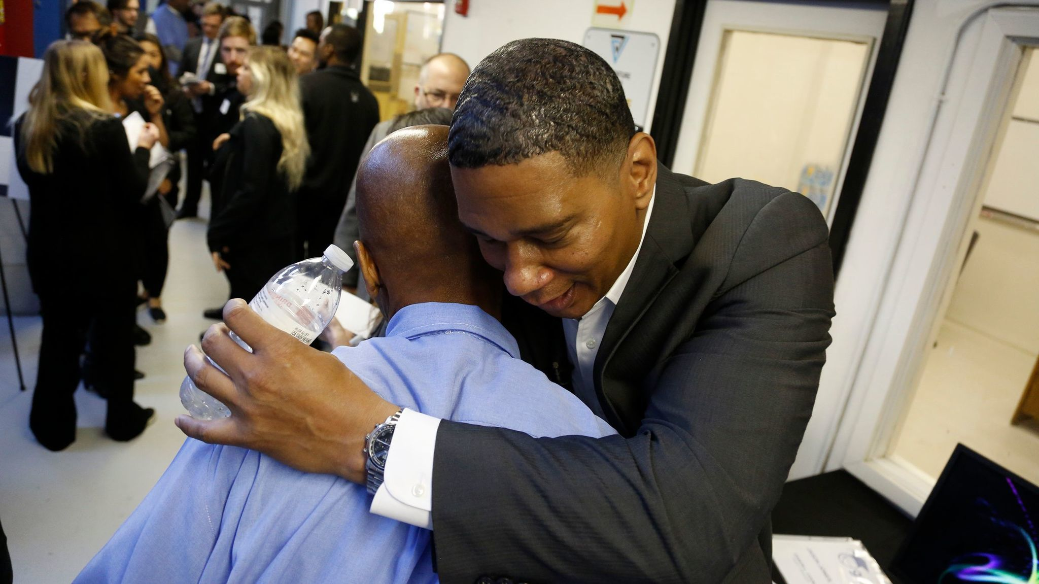 Former inmate Chrisfino Kenyatta hugs a San Quentin inmate after a graduation ceremony for the Last Mile Works where he is currently serving on the board of directors.