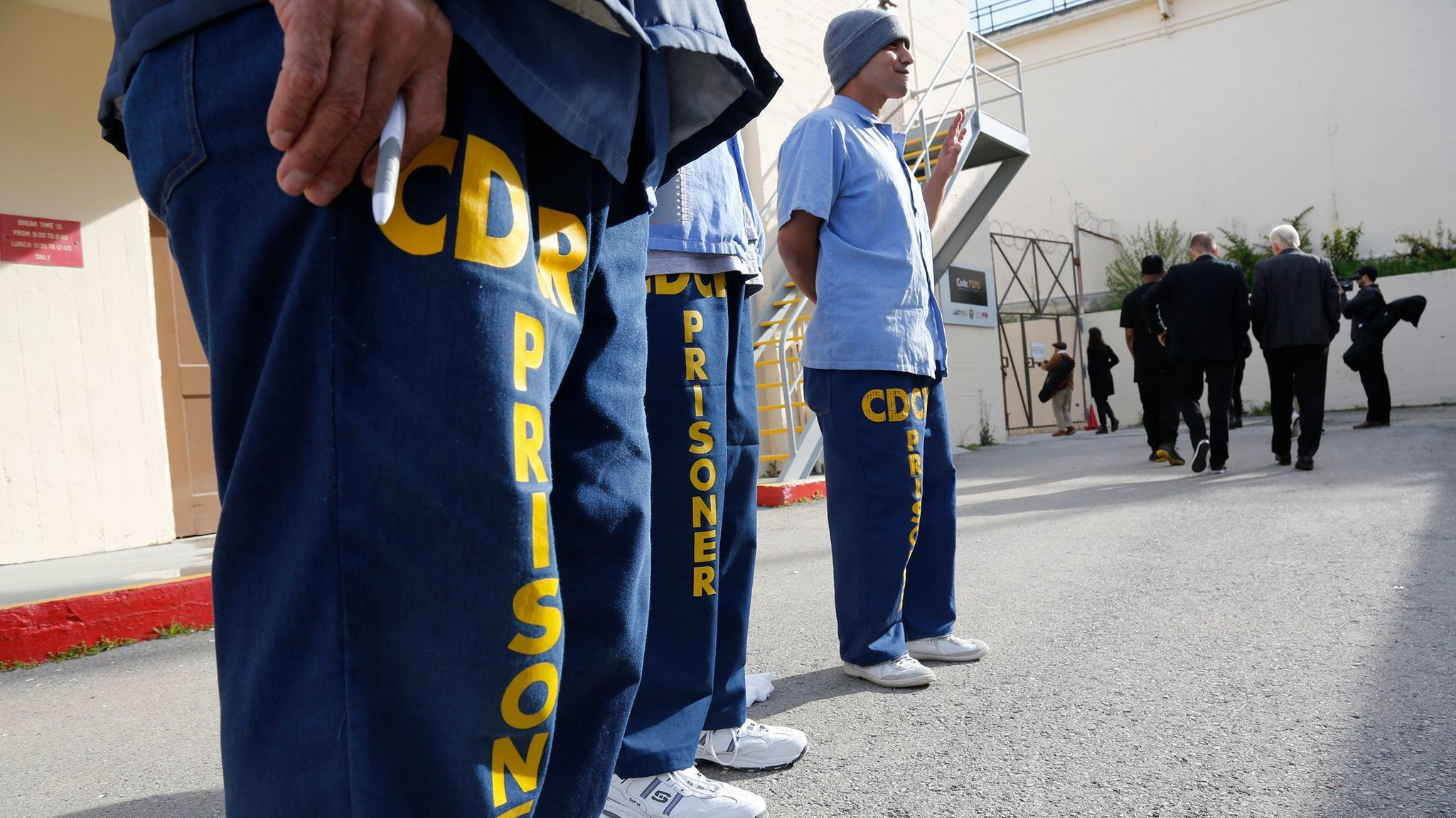 Inmates at San Quentin greet visitors arriving for graduation ceremonies for the Last Mile Works program.