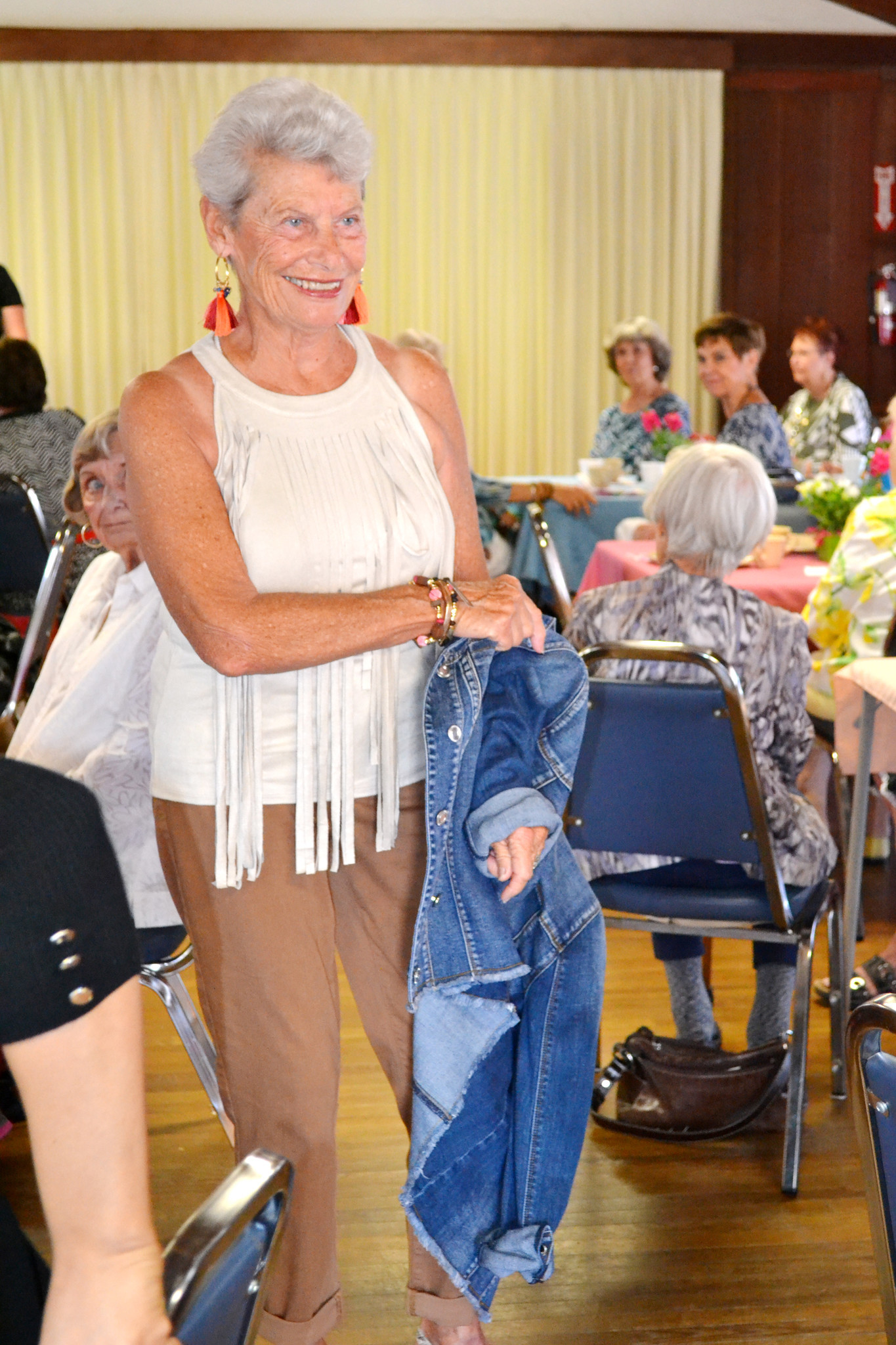 Sandy Bedard takes off her denim jacket to show luncheon guests the fringe top she wears underneath.