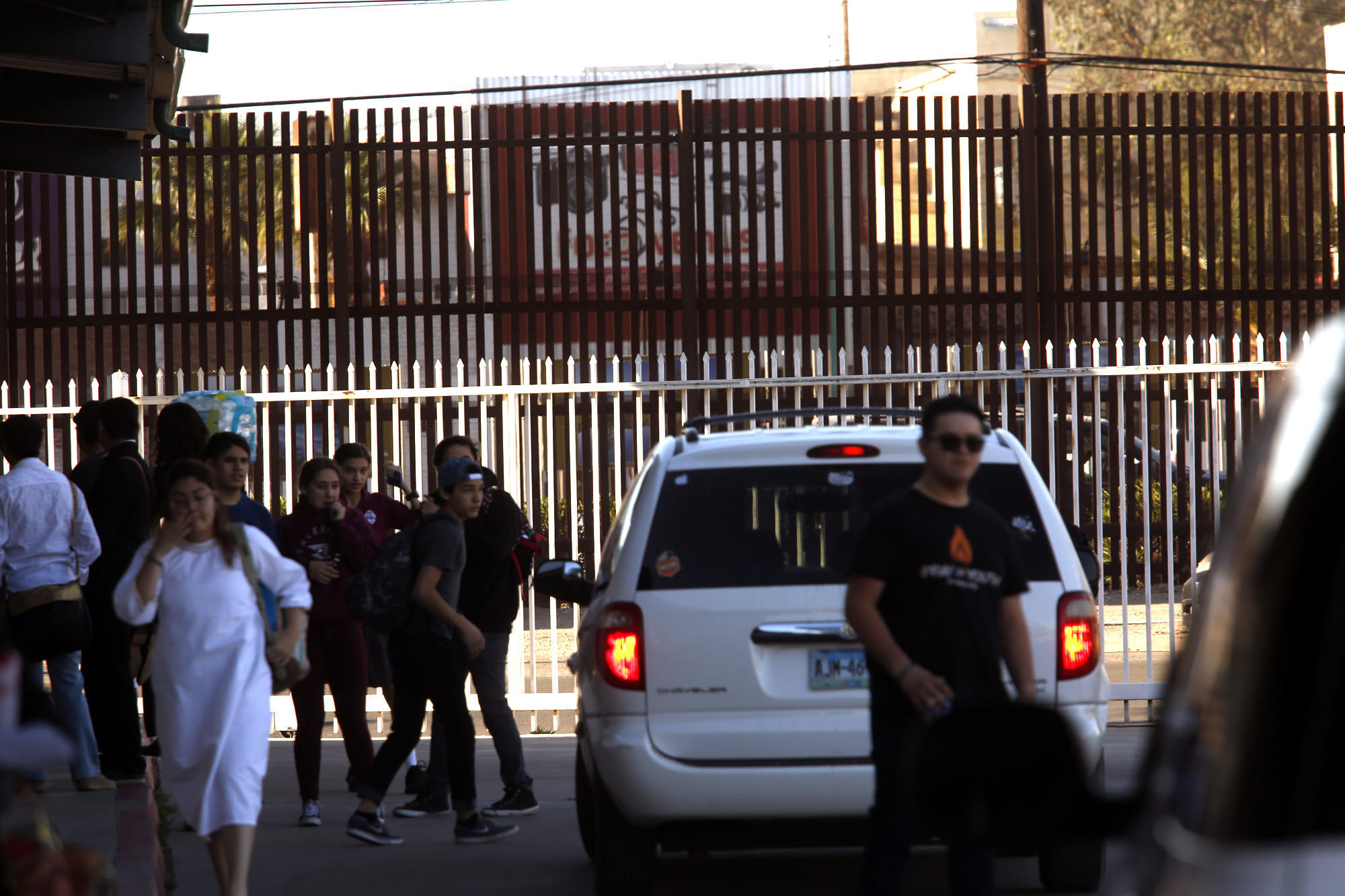 Students are dropped off and picked up in an area framed by the school fence in white and the brown U.S.-Mexico border fence.