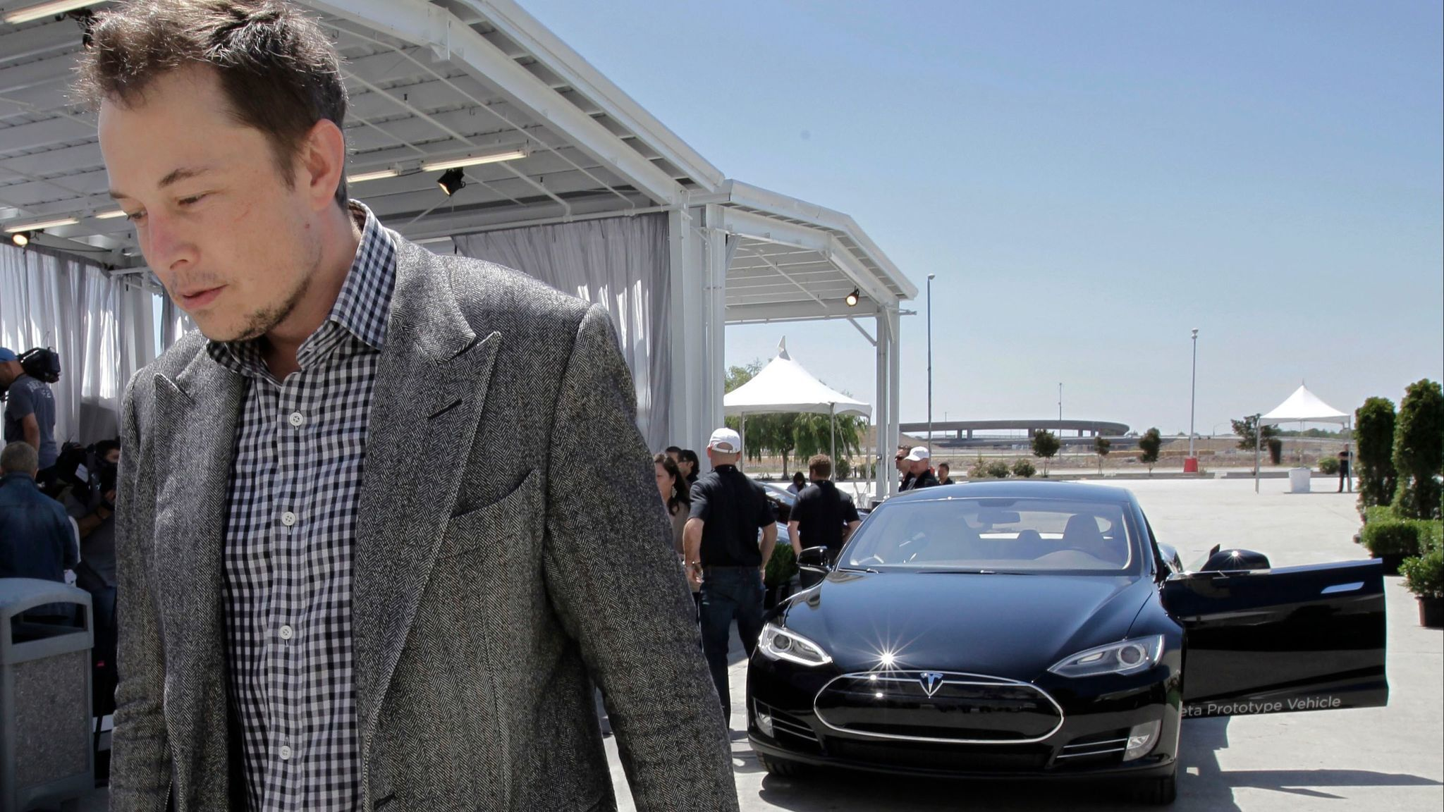 Elon Musk is seen in 2012 leaving a news conference where he blamed a shortage of lithium-ion battery cells for trouble meeting demand for the Model S.