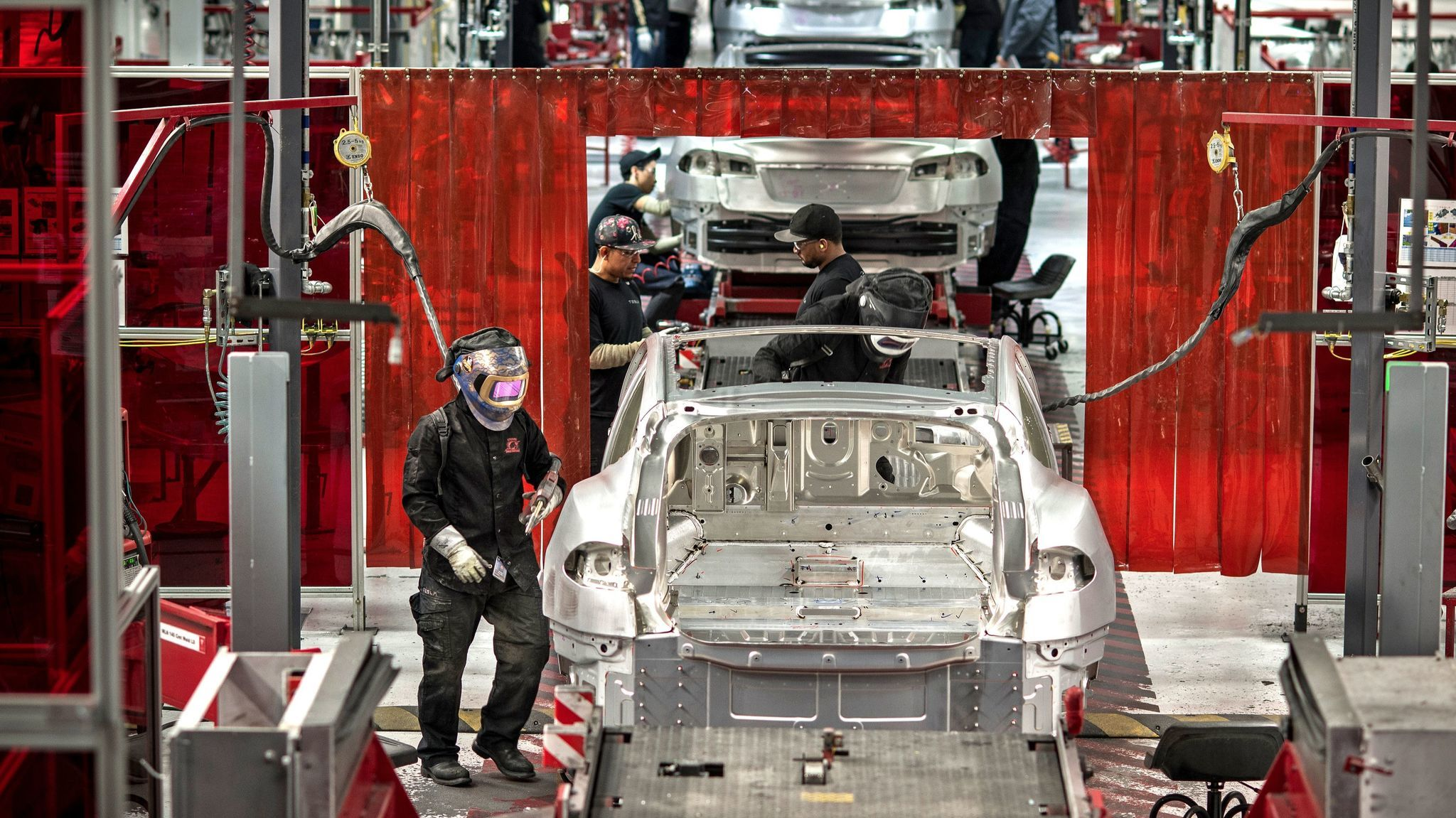 Workers assemble cars at the Tesla factory in Fremont.