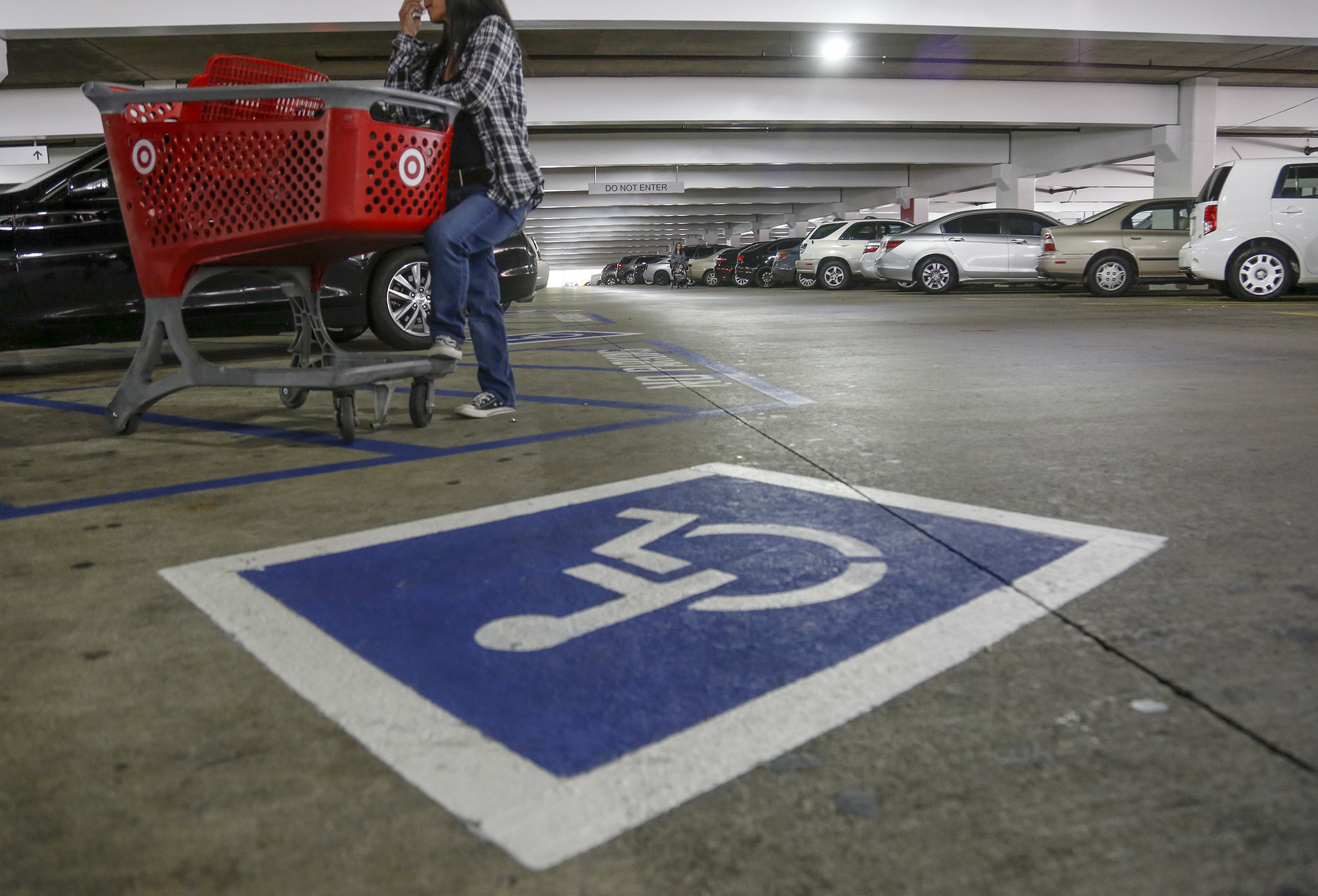 An undercover DMV officer waits with a shopping cart next to a disabled parking spot while conducting an enforcement sweep of fraudulent use of disabled parking placards at the Glendale Galleria. (Mark Boster / Los Angeles Times)
