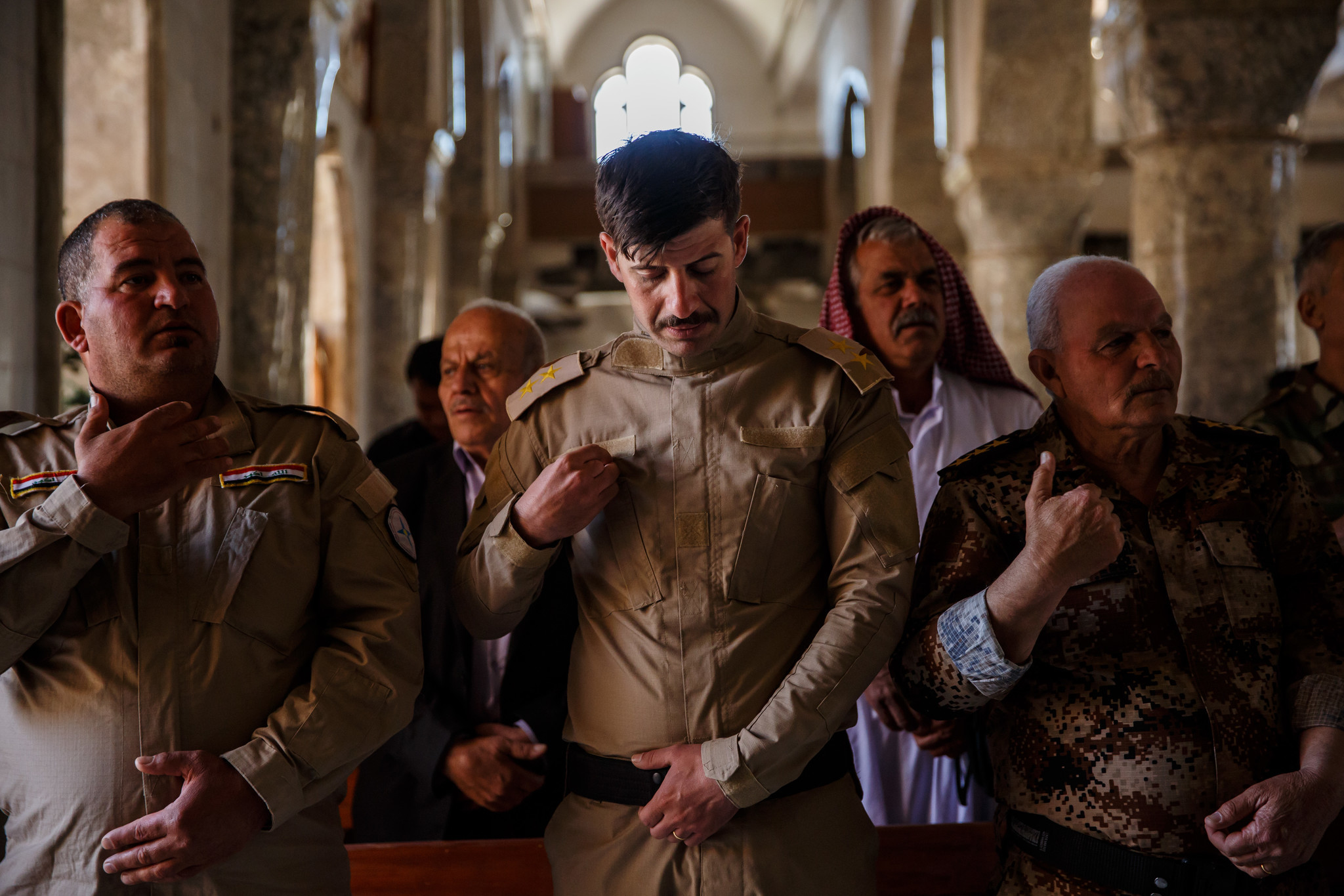Soldiers make the sign of the cross during Easter Mass at the Mar Youhanna Church, also known as St. John Church, in Iraq.
