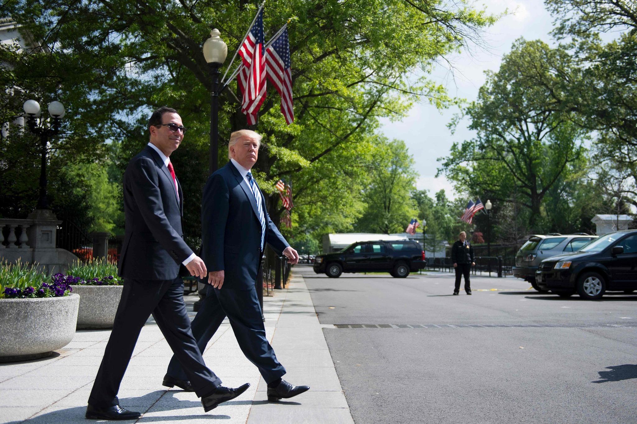 President Trump walks with Treasury Secretary Steven Mnuchin on Friday, April 21. (Jim Watson / AFP/Getty Images)