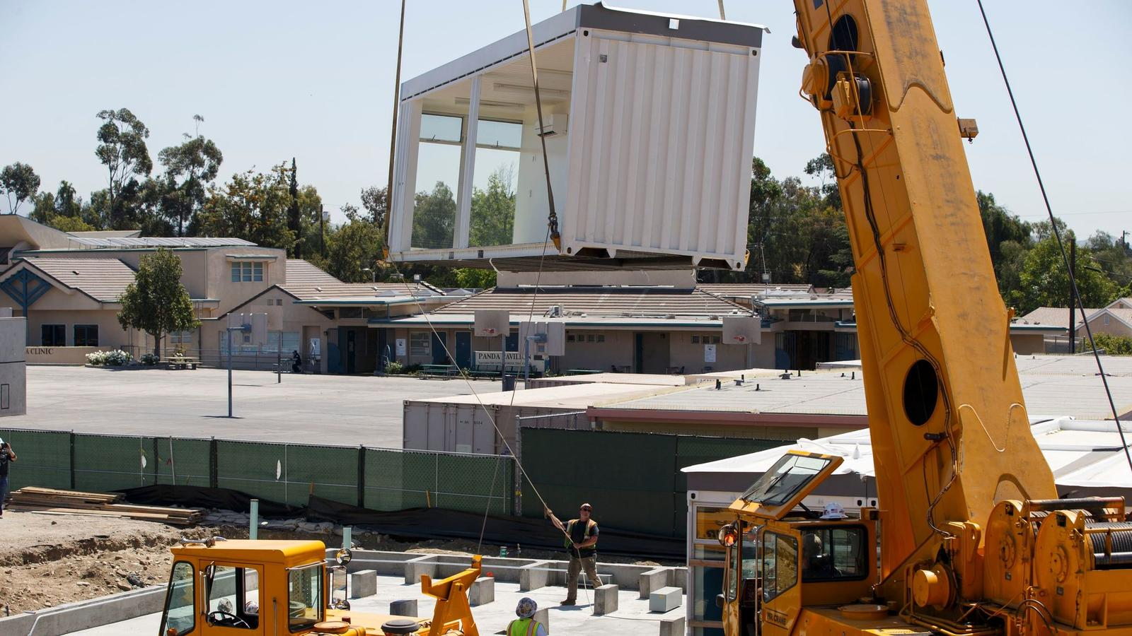 Construction workers use a crane to lift prefabricated classroom sections made of recycled shipping containers into position at Vaughn Next Century Learning Center. (Patrick T. Fallon / For The Times)