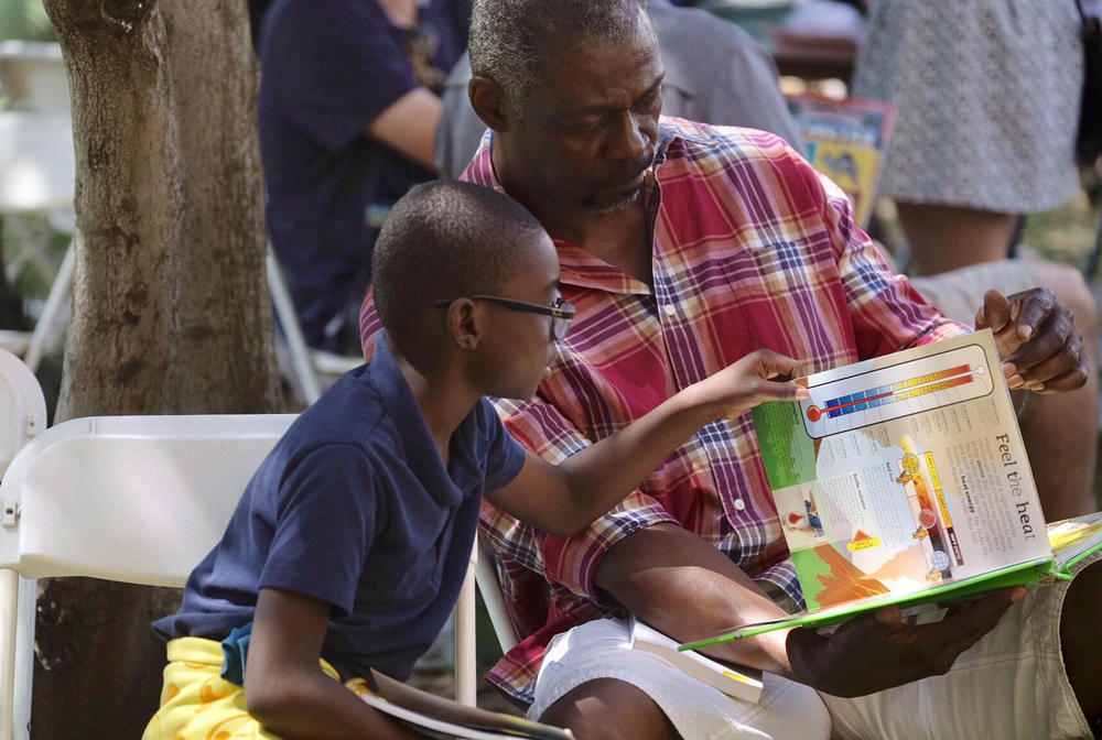 Cameron Morris, 8, reads a book with his grandfather Wayne Richardson on Sunday at USC. (Francine Orr / Los Angeles Times)