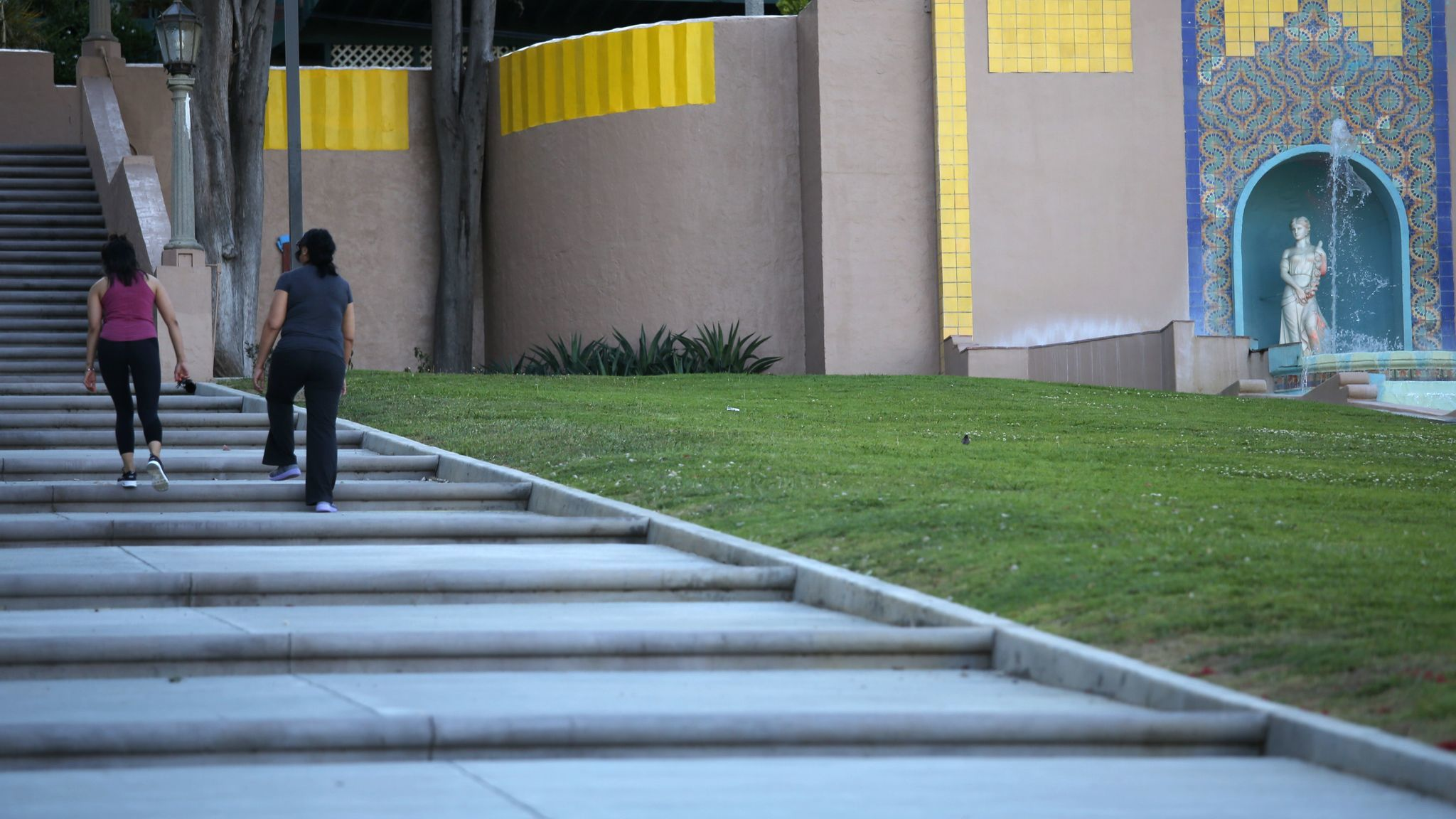 Walkers stroll by the Athena statue that tops the Heritage Falls fountain in Monterey Park.