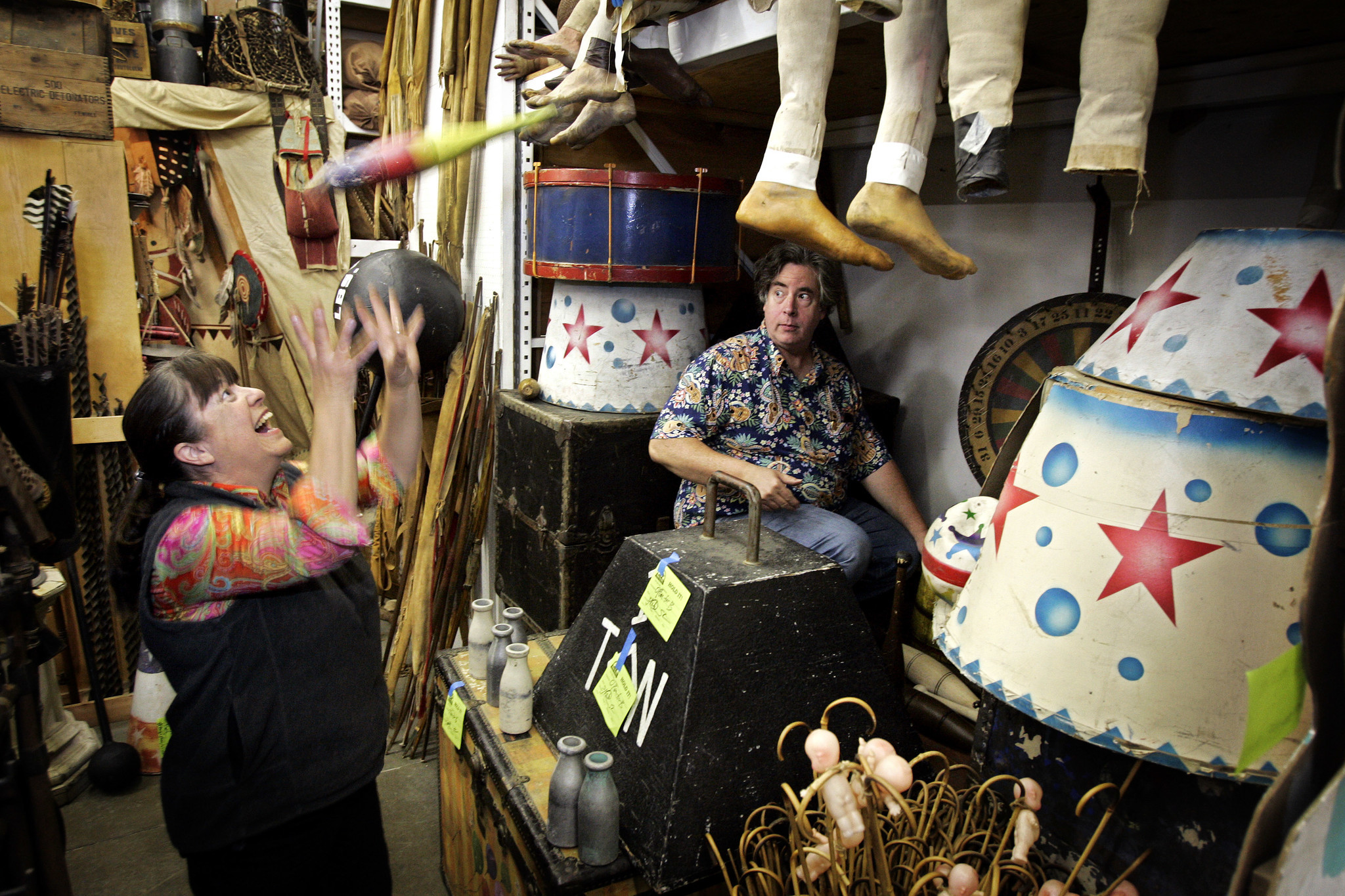 "Pam Elyea catches a juggling pin thrown by her husband, Jim, while gathering props for the film ""Water for Elephants"" in 2010 at their store History for Hire, a prop shop specializing in period and historical items."