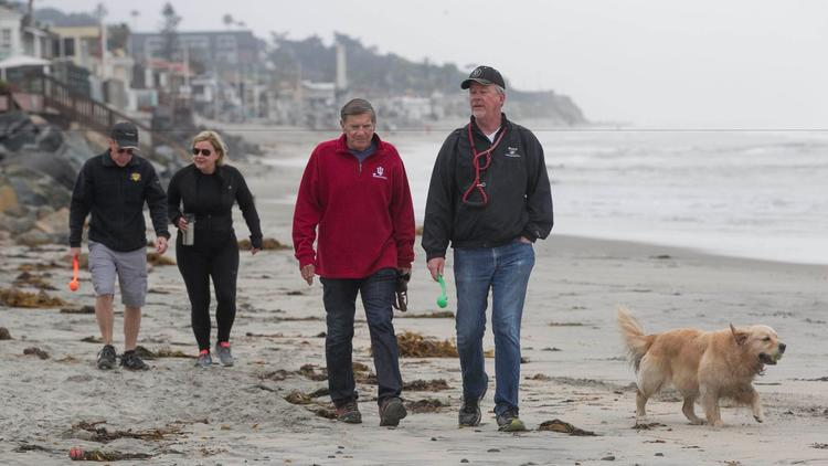 Scott MacDonald, second from right, walks along the beach in Del Mar with friends Pat Steusloff, fro