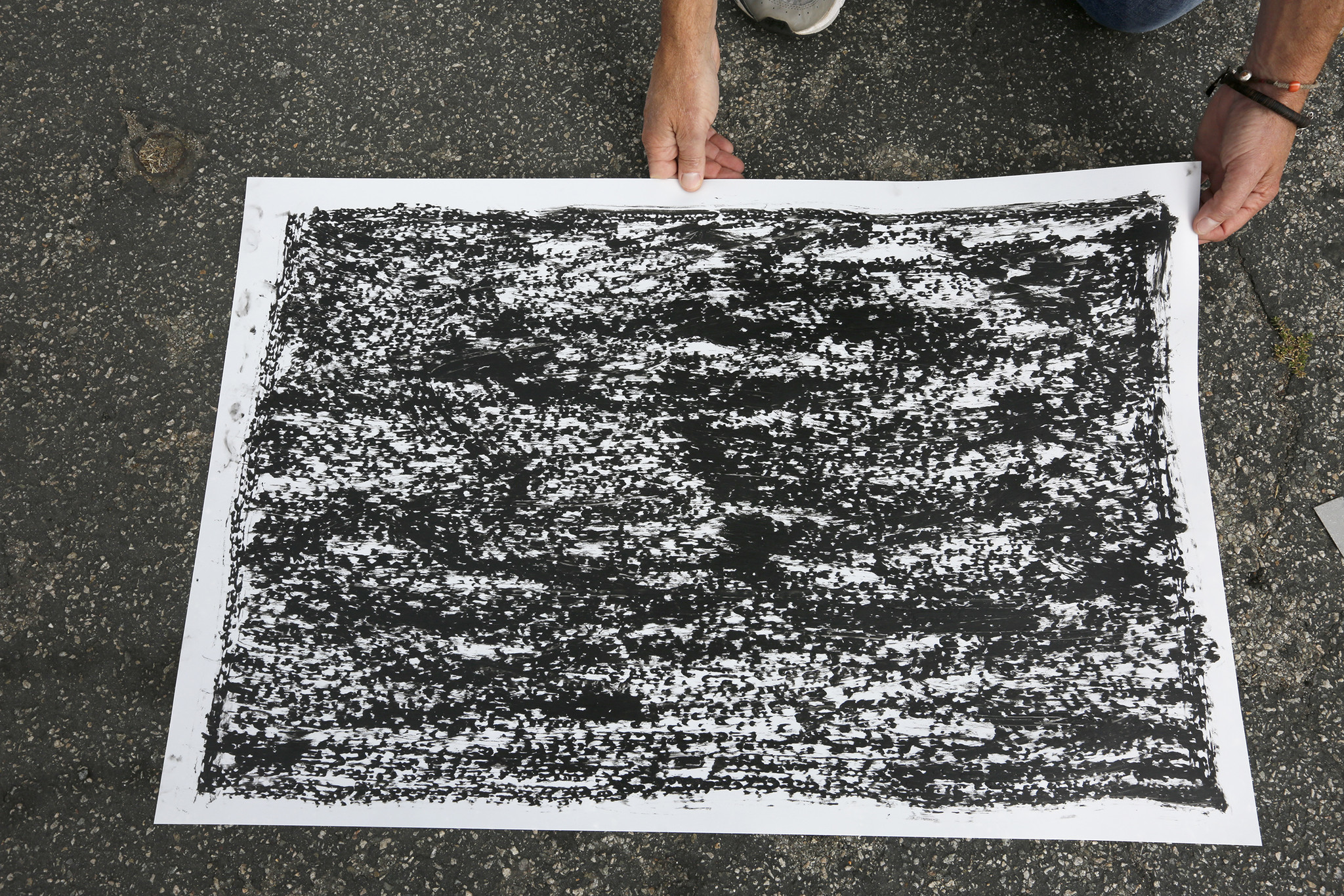 Artist Jeff Beall displays one of the rubbings taken at the site of an unsolved death related to the 1992 L.A. riots — in this case that of a 23-year-old Latino man named Arturo C. Miranda.