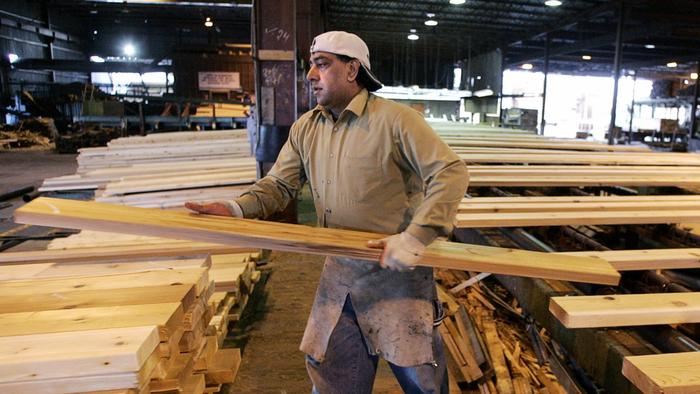 A worker sorts lumber at the Pan Abode Mill in Richmond, Canada. (Chuck Stoody / Associated Press)