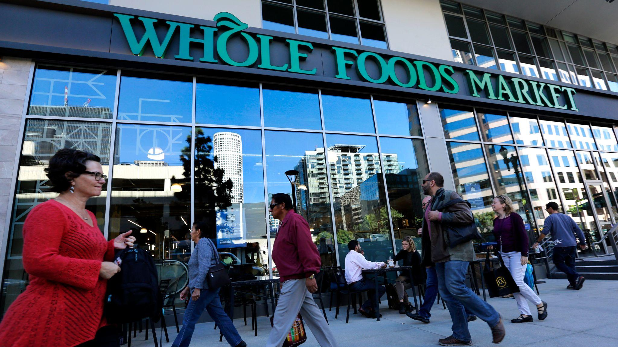 Pedestrians make their way past a Whole Foods Market on Grand Avenue in downtown Los Angeles during the store's grand opening on December 4, 2015.