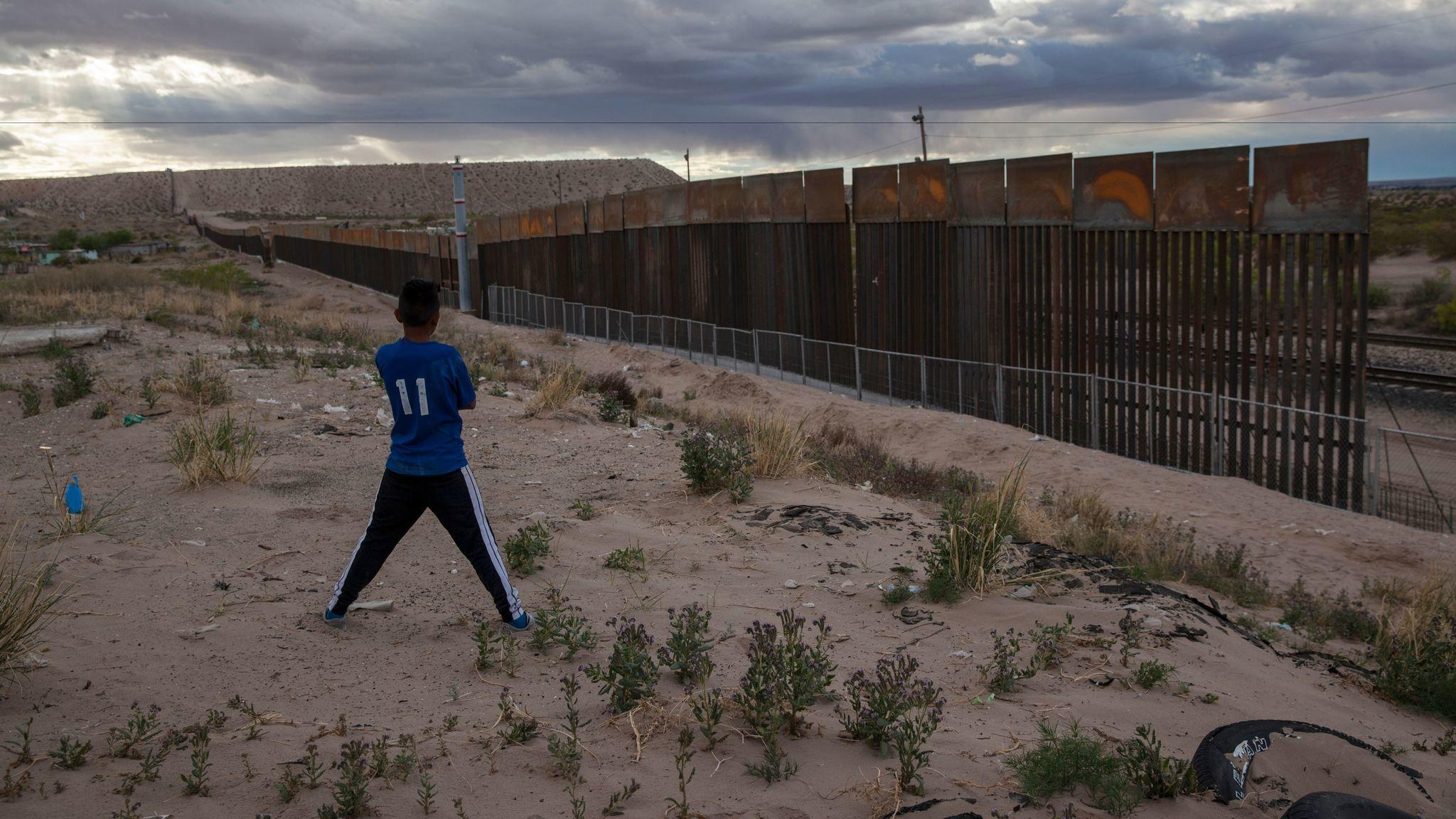 A boy in Ciudad Juarez, Mexico, looks at the area where a taller fence is being built along the U.S.-Mexico border near Sunland Park, N.M., on March 29. (Rodrigo Abd / Associated Press)