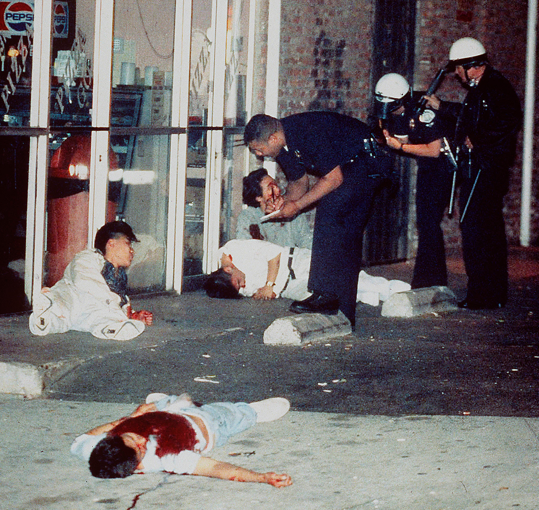 Edward Song Lee, 18, foreground, was shot to death and three other Koreans were injured in an exchange of gunfire with looters at 3rd Street and Hobart Boulevard in Koreatown on April 30, 1992. Police questioned the survivors of the attack who were shot while trying to protect a Korean-owned pizza parlor.