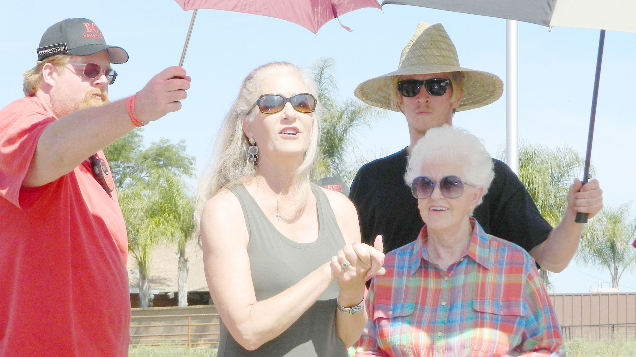 Joined by her mother, Toni Presley, Joyce Battaglia, center, thanks E Clampus Vitus members for their efforts on behalf of the family's historic property a ECV members hold umbrellas to protect the women from the sun.