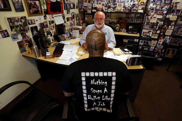 Father Gregory Boyle, founder and director of Homeboy Industries, facing camera, meets with Johnny Chavez in his office at the company's headquarters in Los Angeles on July 10, 2015. (Los Angeles Times)