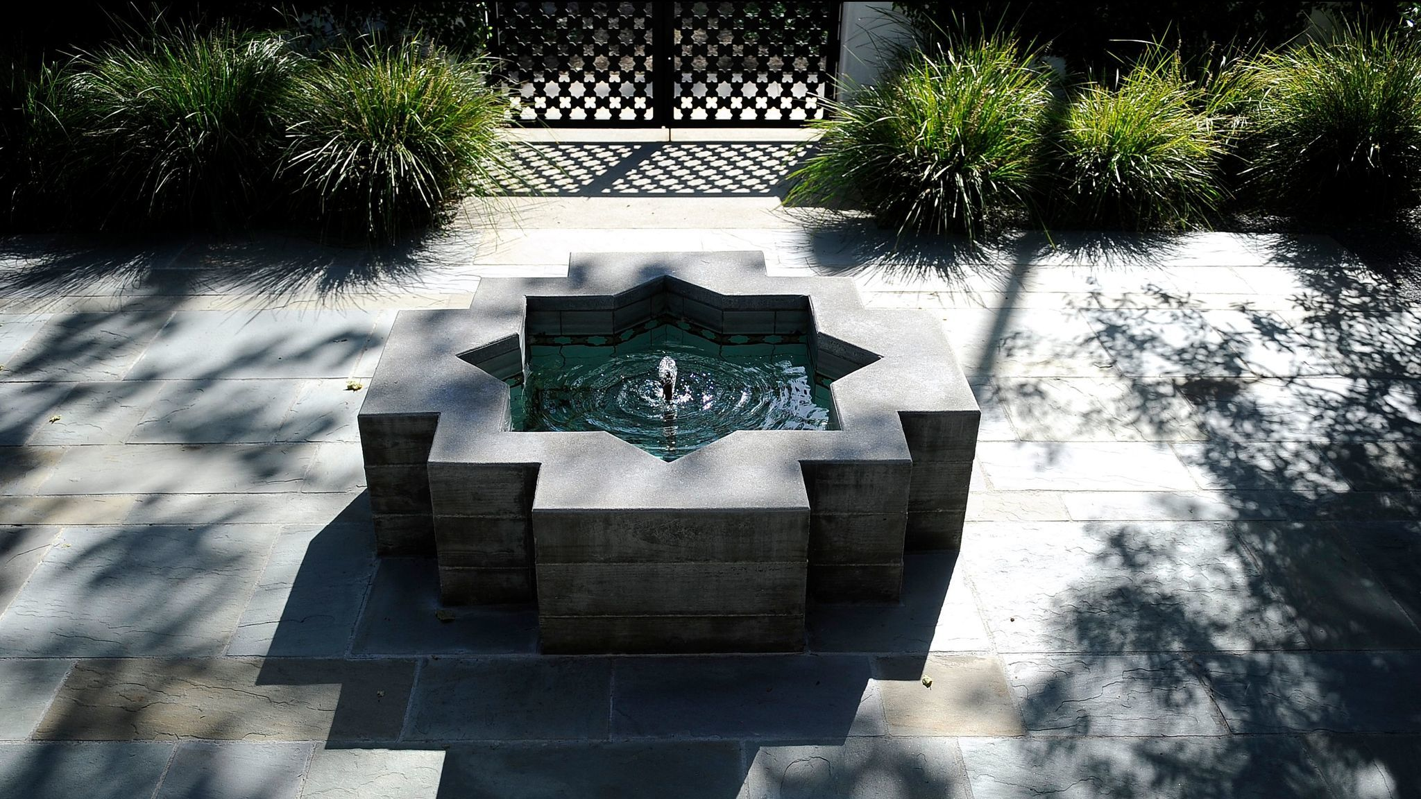A Moroccan-inspired water fountain adds character to the small courtyard in front.