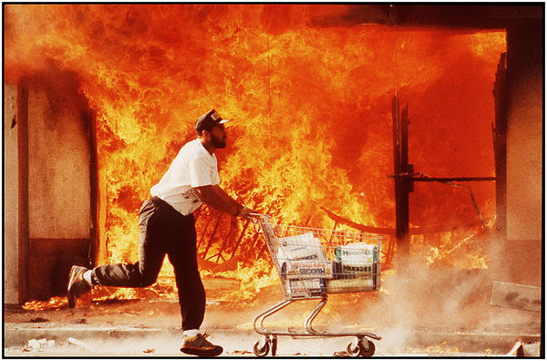 A man runs by buildings engulfed in flame after rioting erupted in L.A. following the 1992 not-guilty verdict for officers charged in Rodney King s beating. (Los Angeles Times)