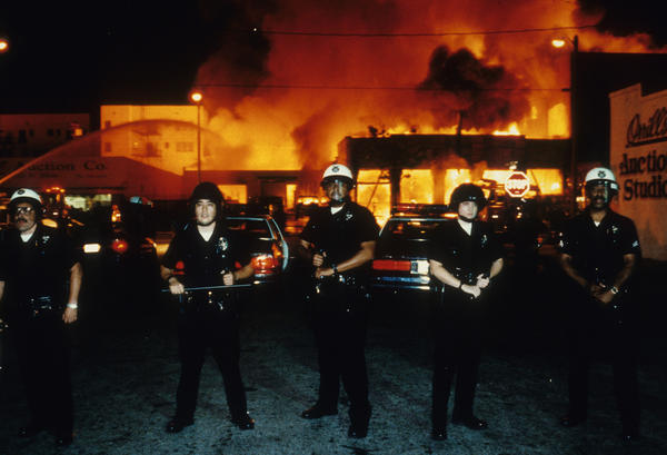 Officers stand guard as fire units battle a blaze near 19th Street and Adams Boulevard on April 30, 1992. (Los Angeles Times)