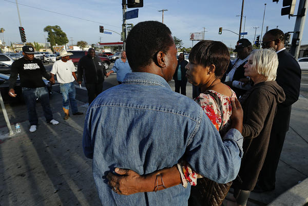 Family members of Latasha Harlins, with South Los Angeles civil rights leaders and clergy, gather to hold a prayer vigil for those who lost their lives in the 1992 riots. (Los Angeles Times)