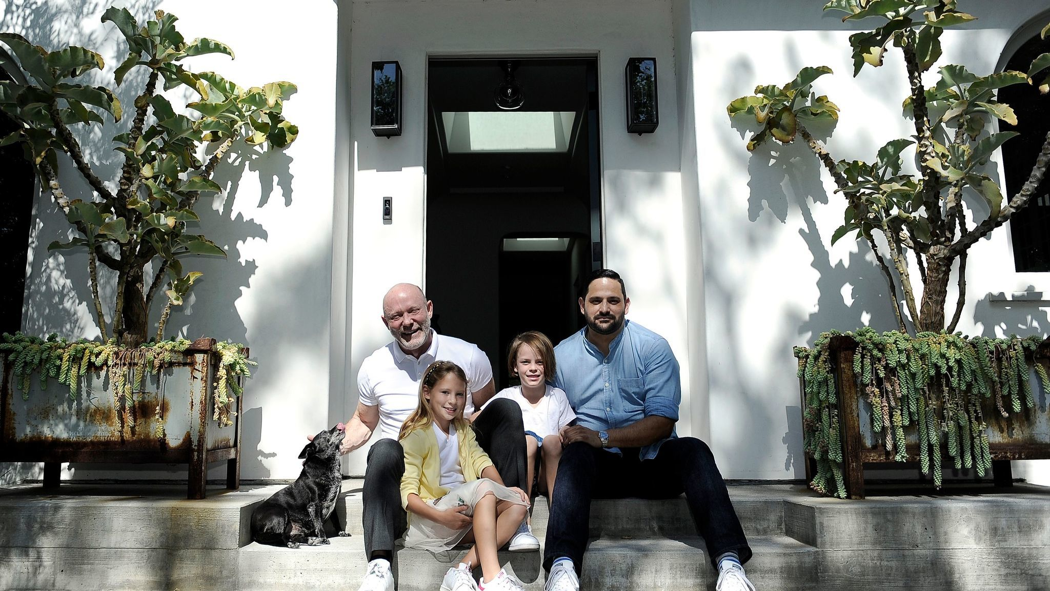 David Collins, left, his daughters Olive and Ella, and David's partner, Joseph Rivas, sit between potted succulents on either side of the front door, which welcome guests in dramatic fashion.