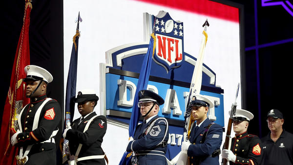 A military color guard marches to the stage before the start of the NFL draft. (Elsa / Getty Images)