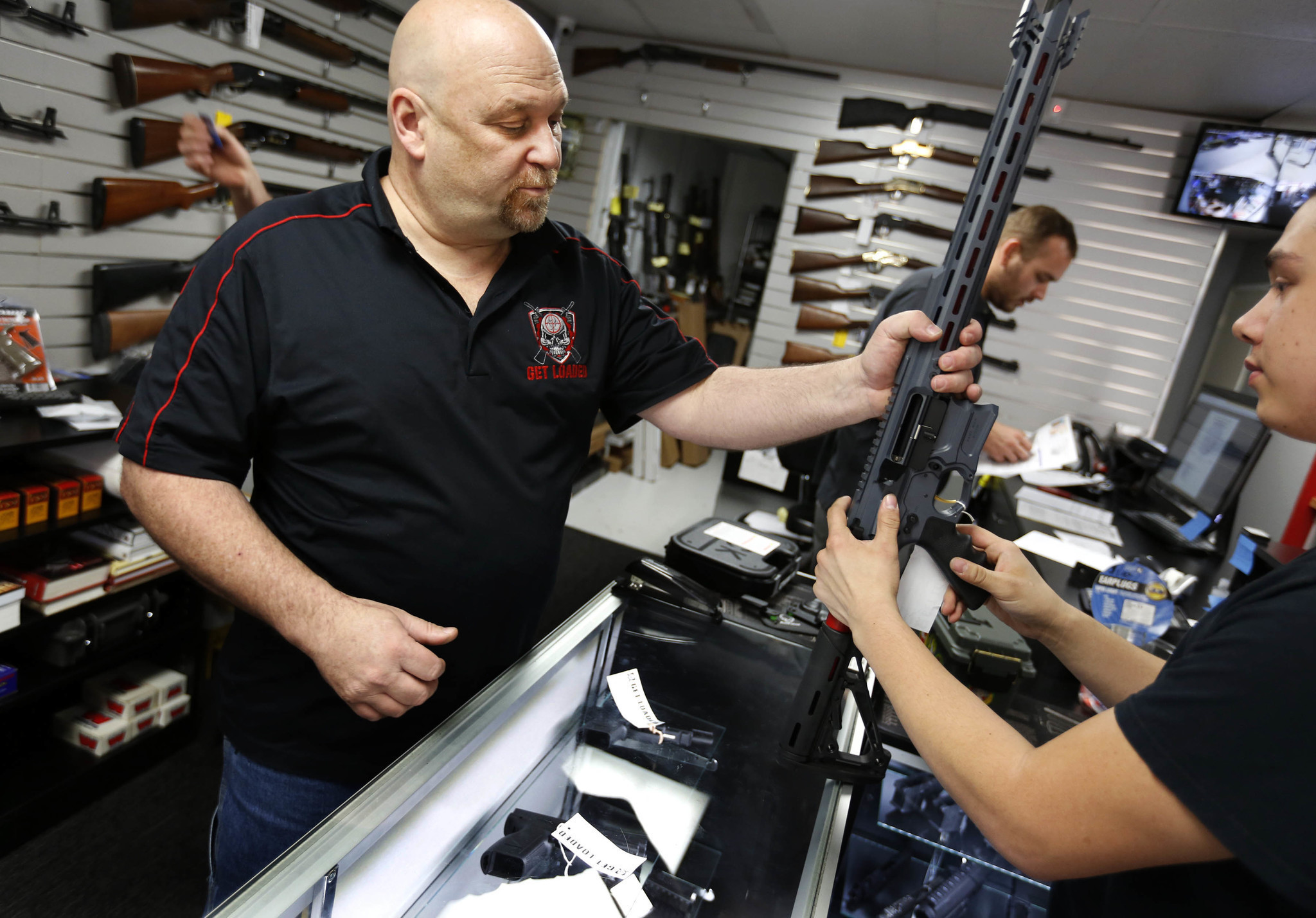 Terry McGuire, owner of Get Loaded in Grand Terrace, shows a customer a Cobalt Kinetics BAMF rifle about a week after the 2015 shooting rampage in nearby San Bernardino. (Barbara Davidson / Los Angeles Times)
