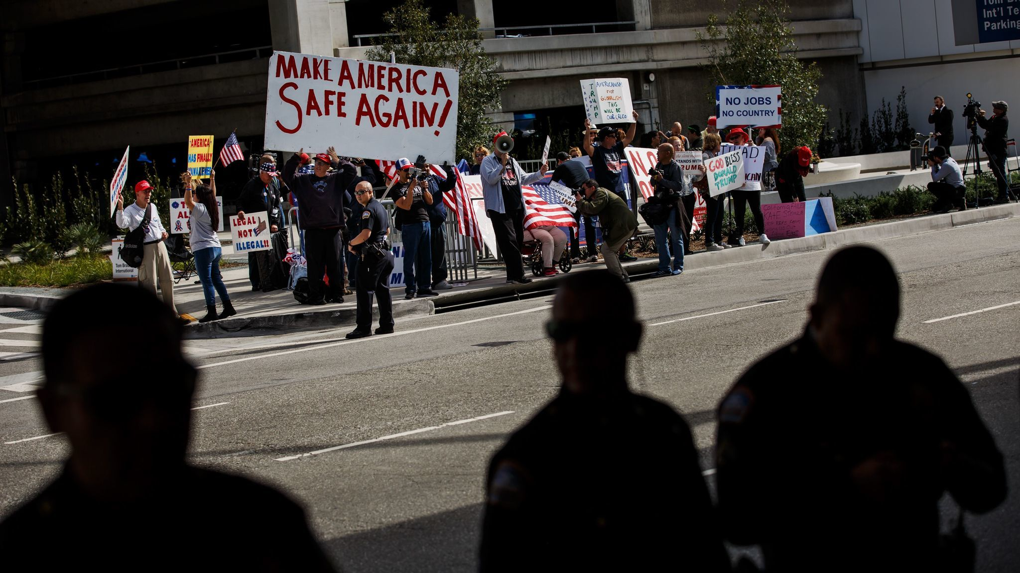 Protesters who support the travel ban stand across the street from the #NoBanNoWall protesters at Los Angeles International Airport on Feb. 4, 2017.