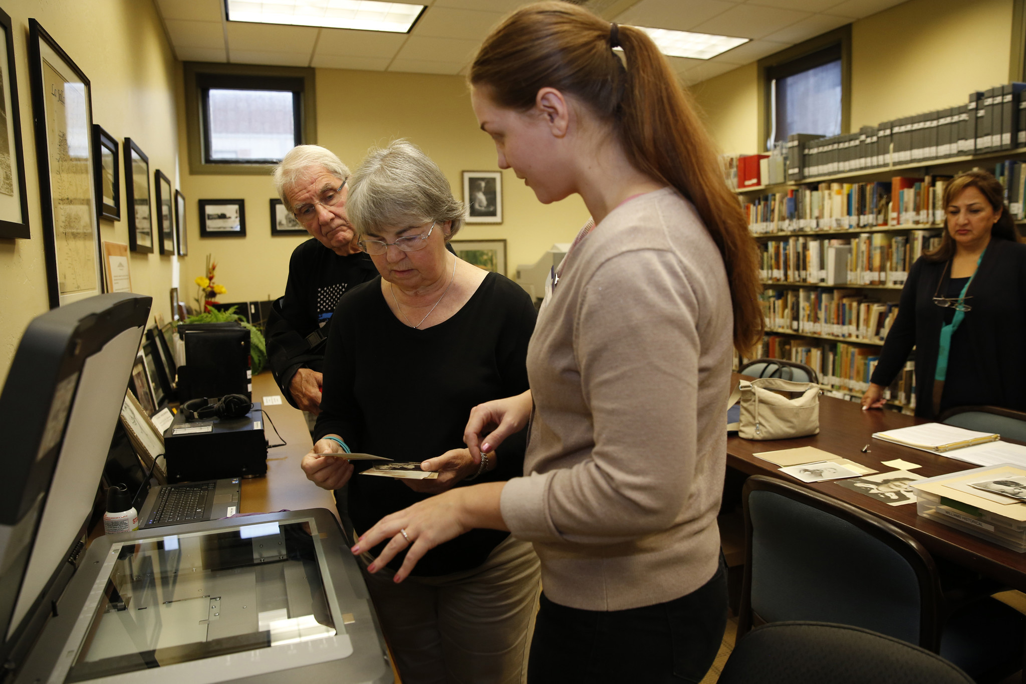 Library assistant Dana Sneberger gives Debbie Hill-Williams (center) and her husband, Bob Williams, hands-on instruction at the new Memory Lab at the La Jolla-Riford Library. Patrons can use software to convert their VHS tapes, photos and other keepsakes to a digital format. (Nancee E. Lewis)