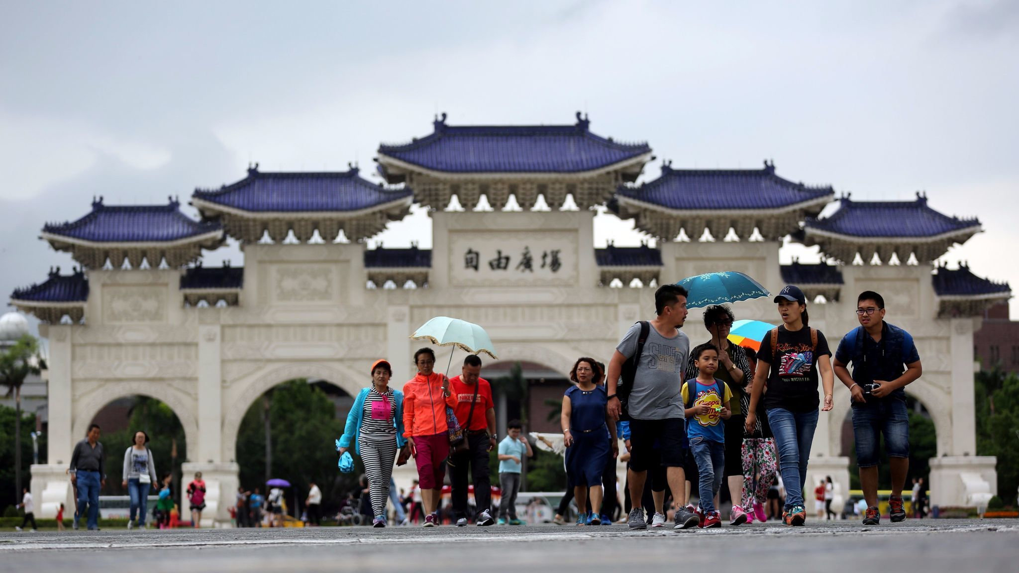 Chinese tourists walk outside the Chiang Kai-shek memorial hall in Taipei, Taiwan, on April 19, 2017.