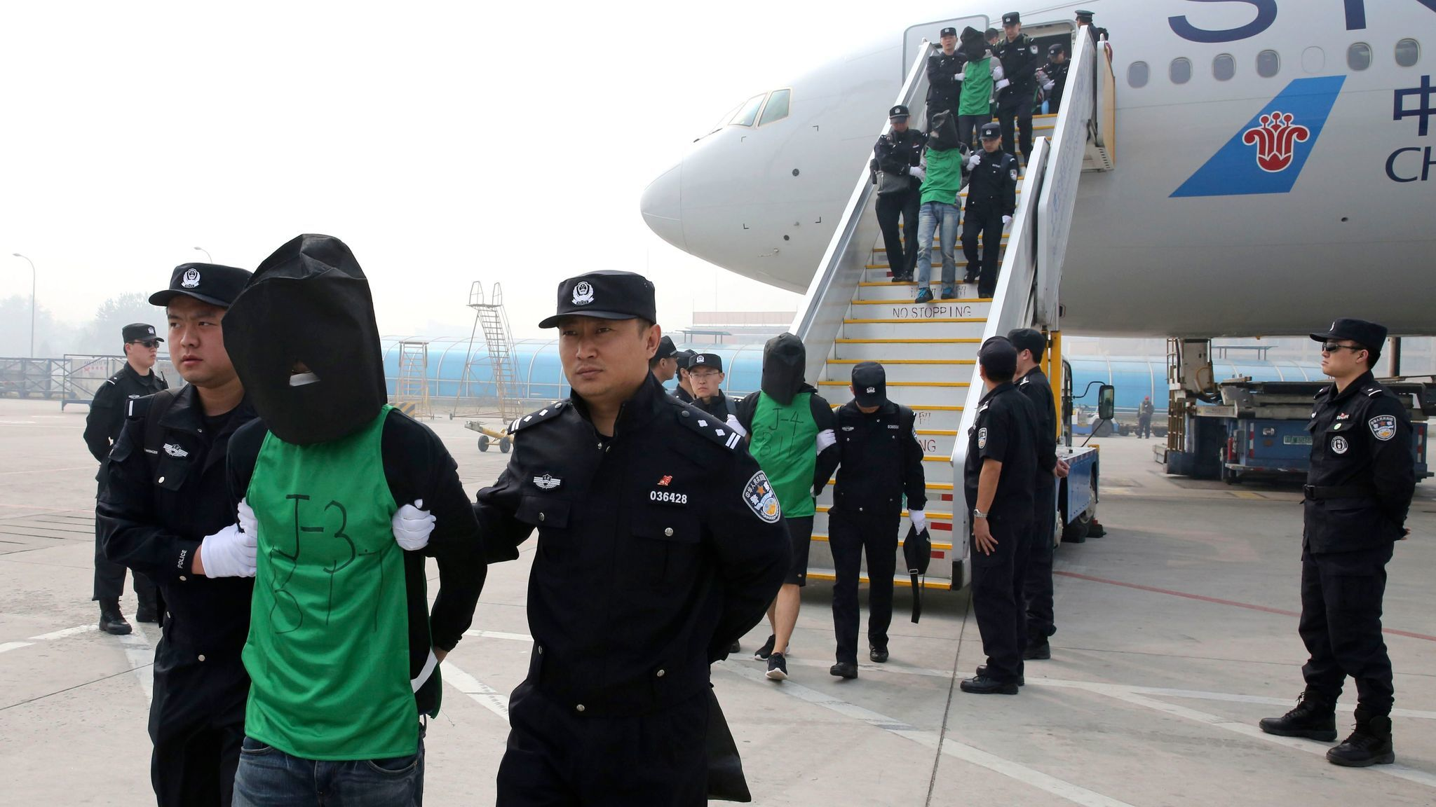 In this photo released by Xinhua News Agency, Chinese suspects involved in wire fraud are escorted off a plane after arriving at the Beijing Capital International Airport on April 13, 2016.