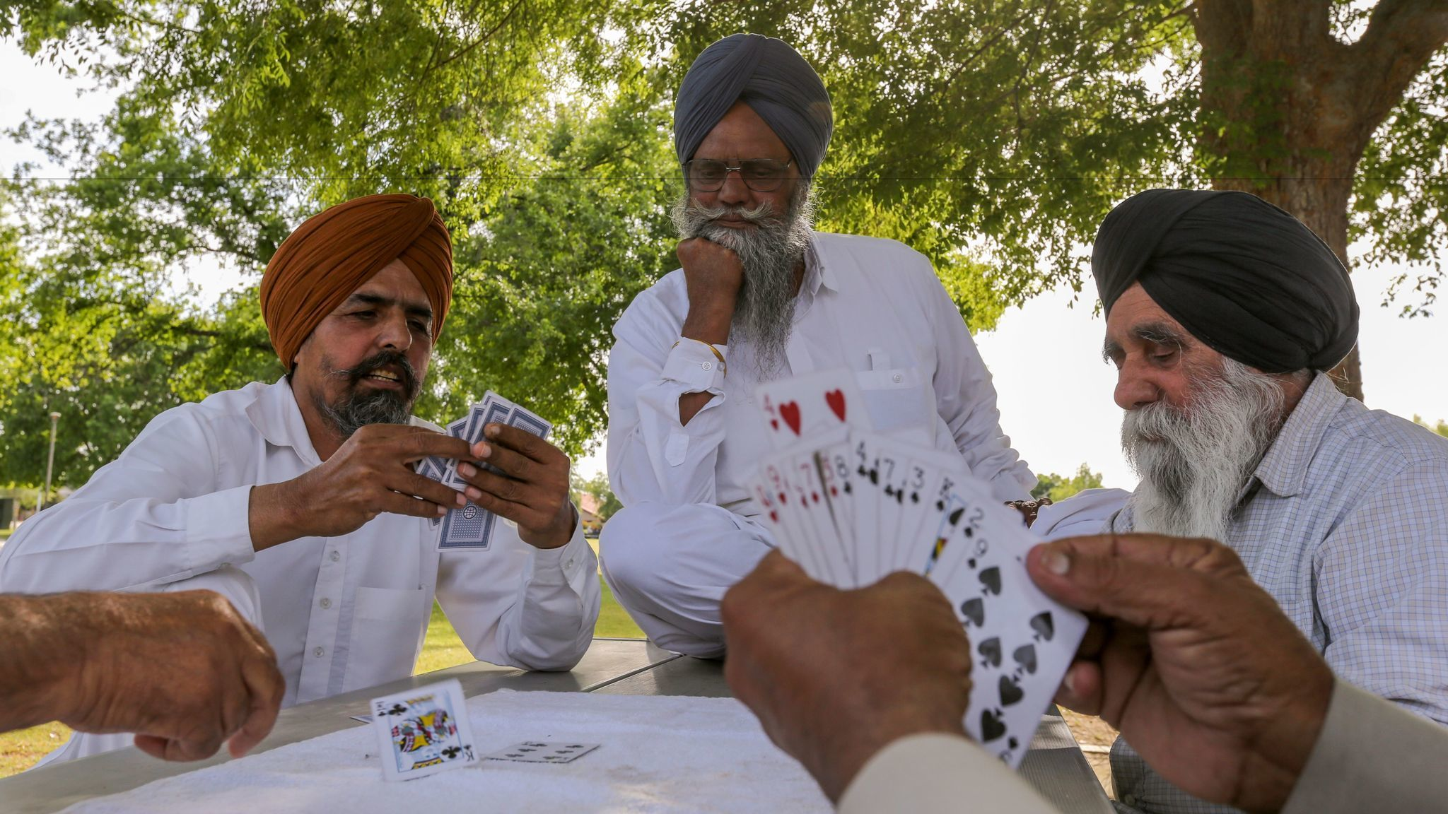 Sikh men play a card game in a neighborhood park in Bakersfield.