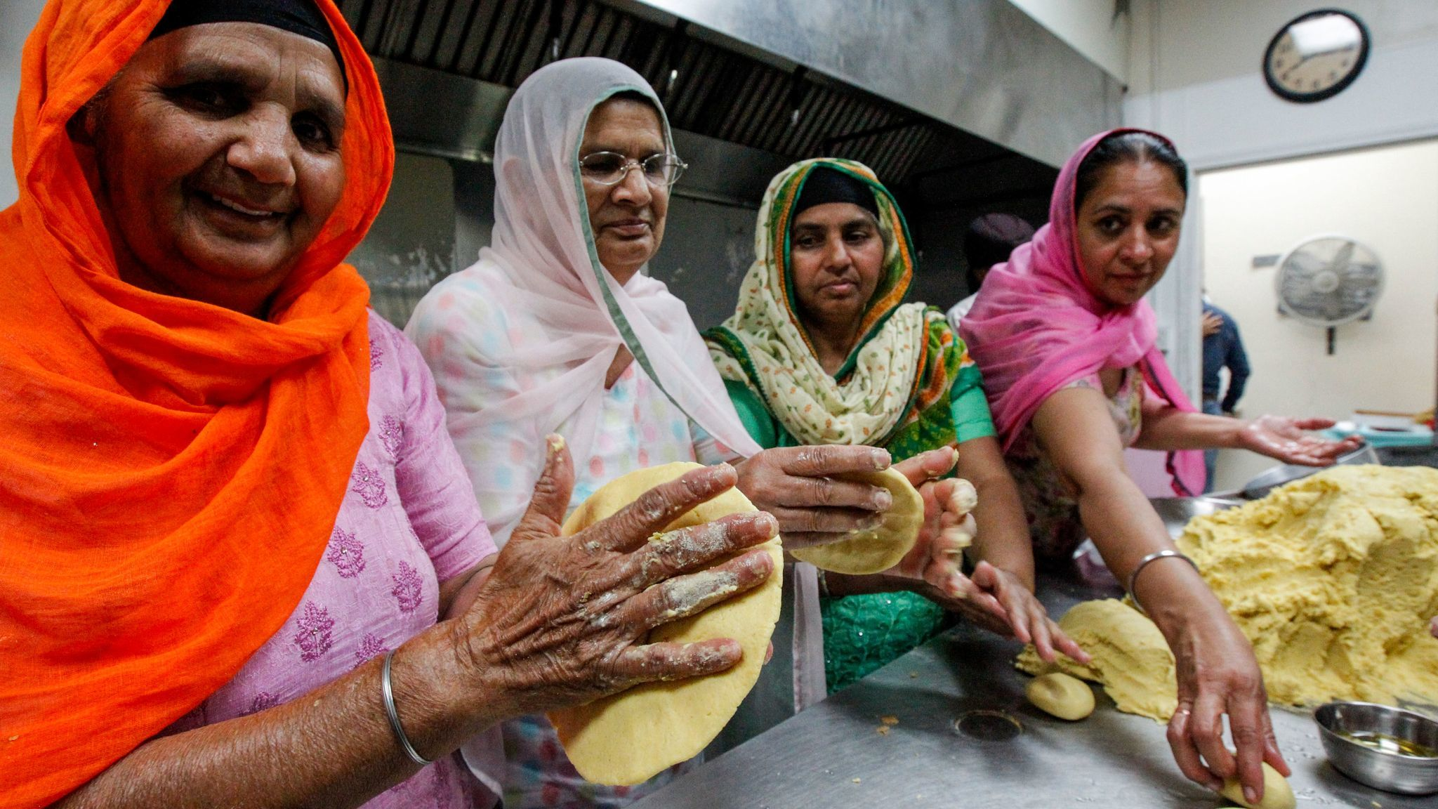 Sikh women prepare bread during Nagar Kirtan celebrations at Gurdwara Guru Angad Darbar in Bakersfield.